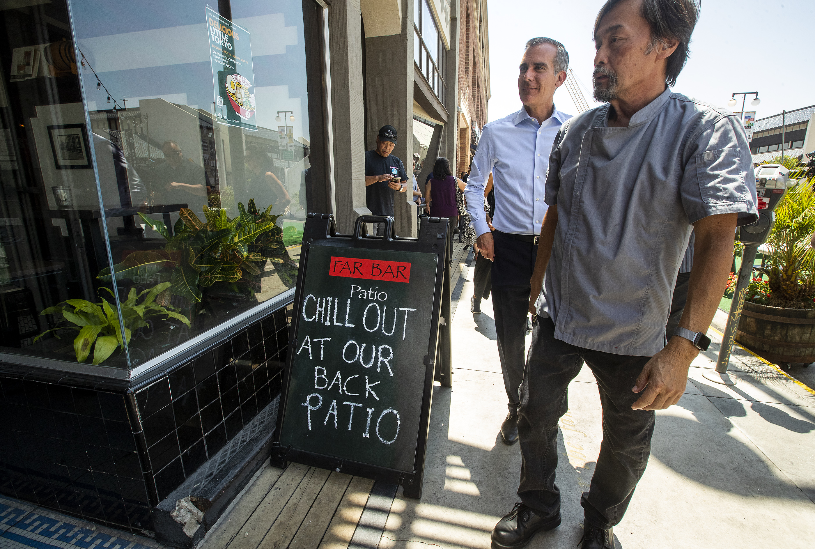Don Tahara, right, owner of Far Bar restaurant on 1st St. in the Little Tokyo section of Los Angeles, gives a tour of his establishment to Los Angeles Mayor Eric Garcetti.