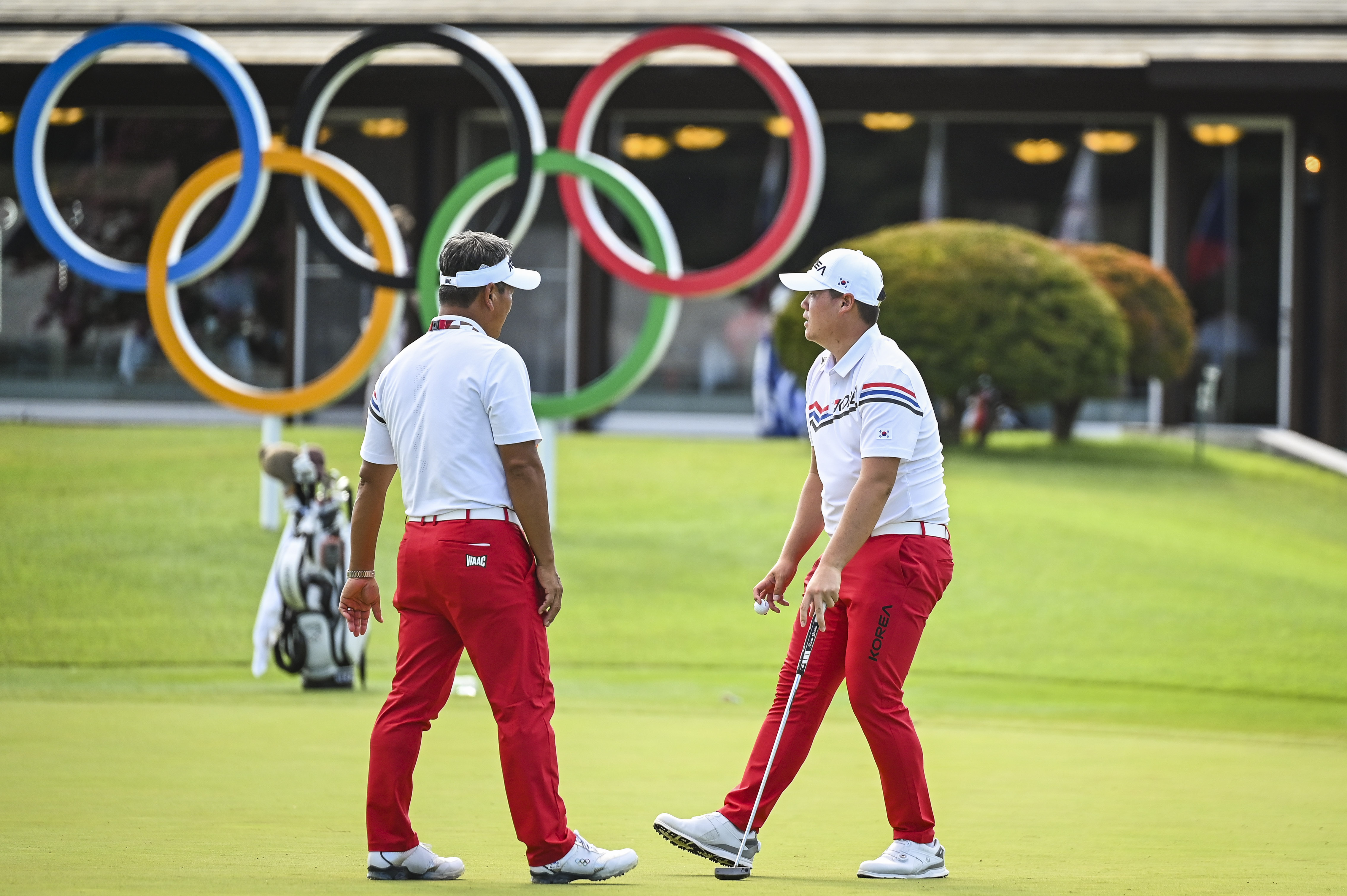 Sungjae Im and K.J. Choi of Team South Korea work on the putting green in front of the Olympic Rings during practice for the Mens Golf Competition of the Tokyo Olympic Games on the East Course at Kasumigaseki Country Club on July 27, 2021 in Kawagoe, Saitama, Japan.
