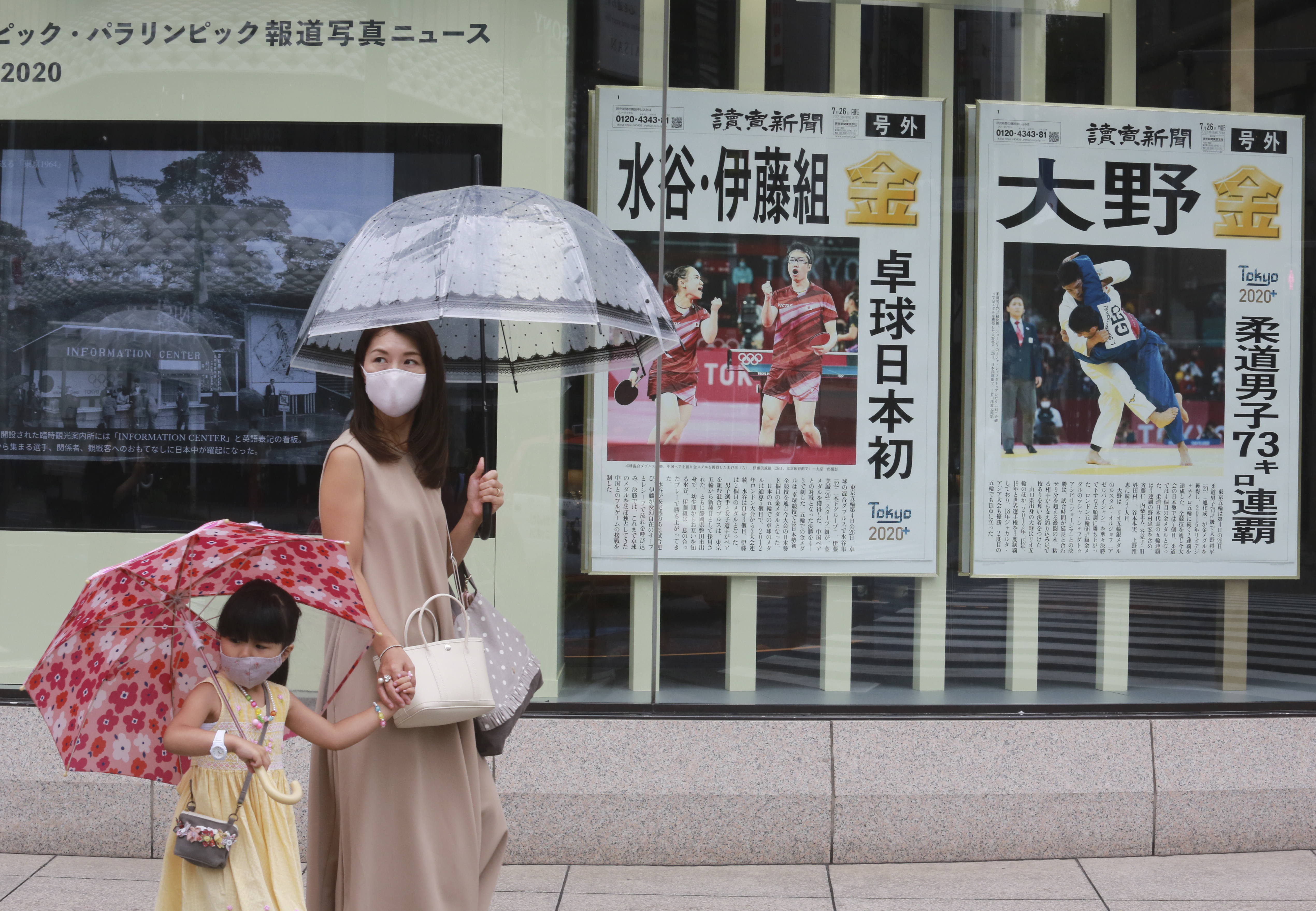 People wearing face masks walk past extra papers reporting on Japanese gold medalists at Tokyo Olympics.