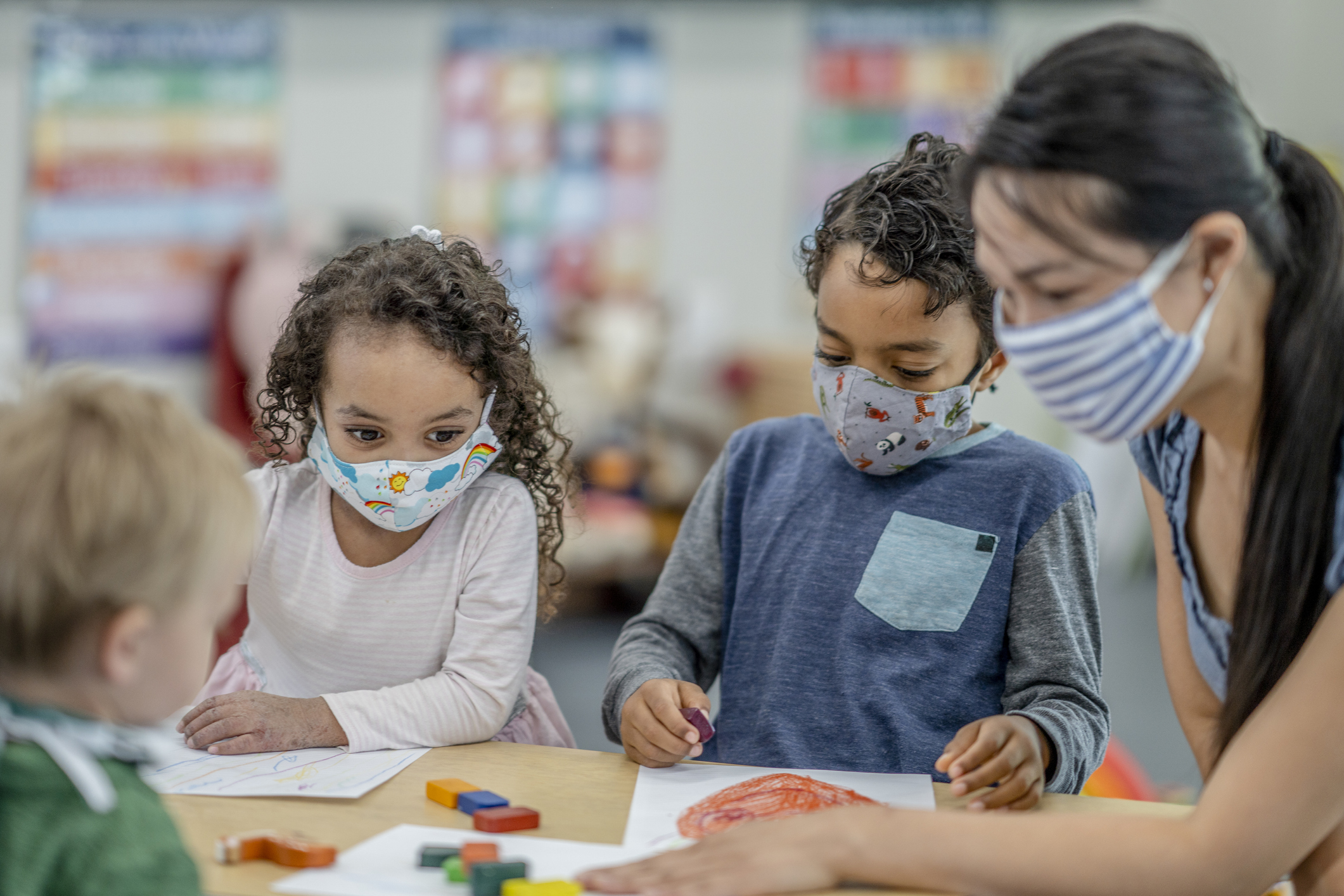 Children coloring at a table while wearing protective face masks.