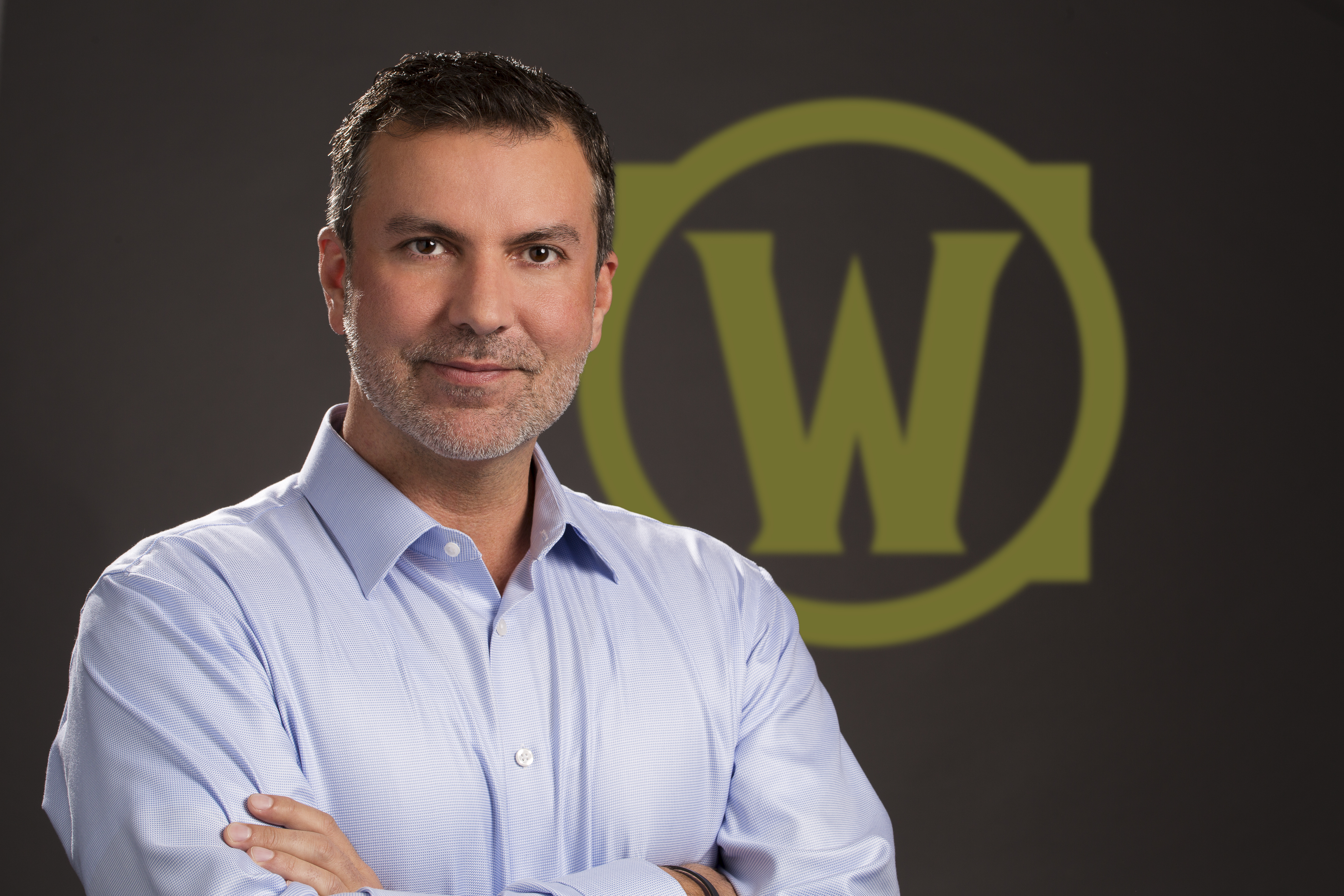 A press photo of former World of Warcraft creative director Alex Afrasiabi in front of the game's logo.