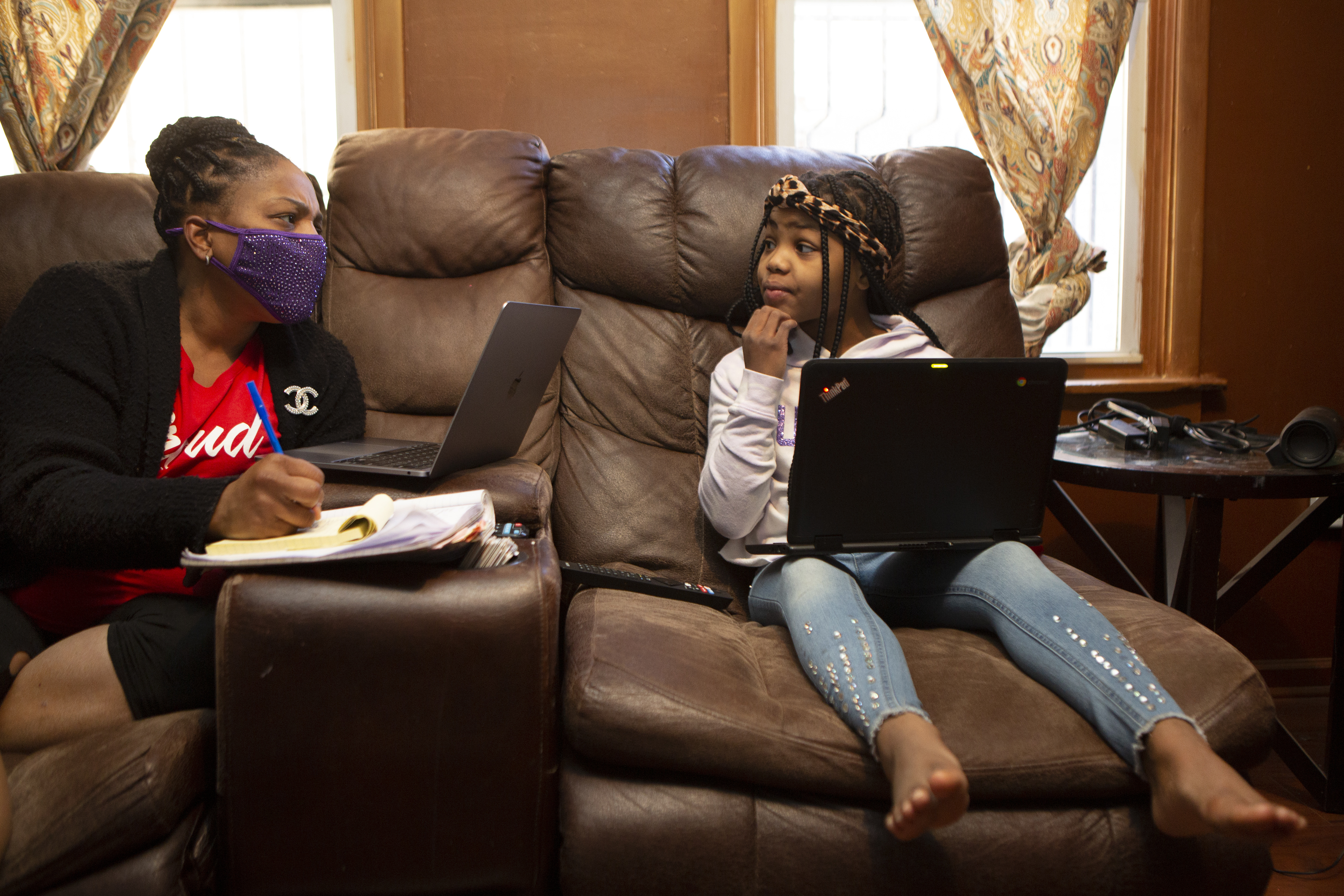 Joicki Floyd starts her day for Weequahic High School remotely and also chats with her daughter Donnell as she also prepares for her own remote learning from their home in Newark on Wednesday morning, Mar. 3, 2021.