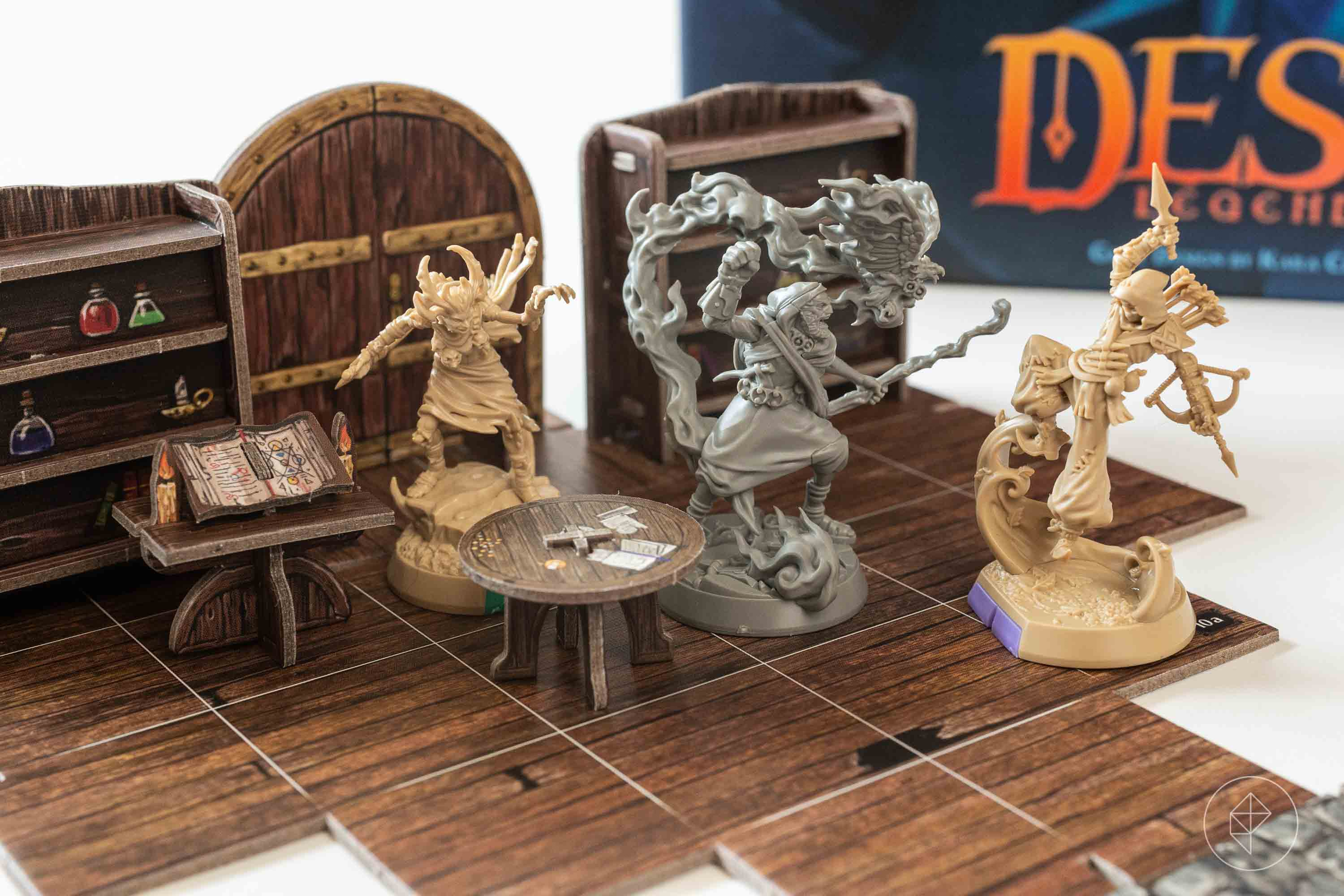 A wizard miniature casts a spell against a pirate and a hag in a library.