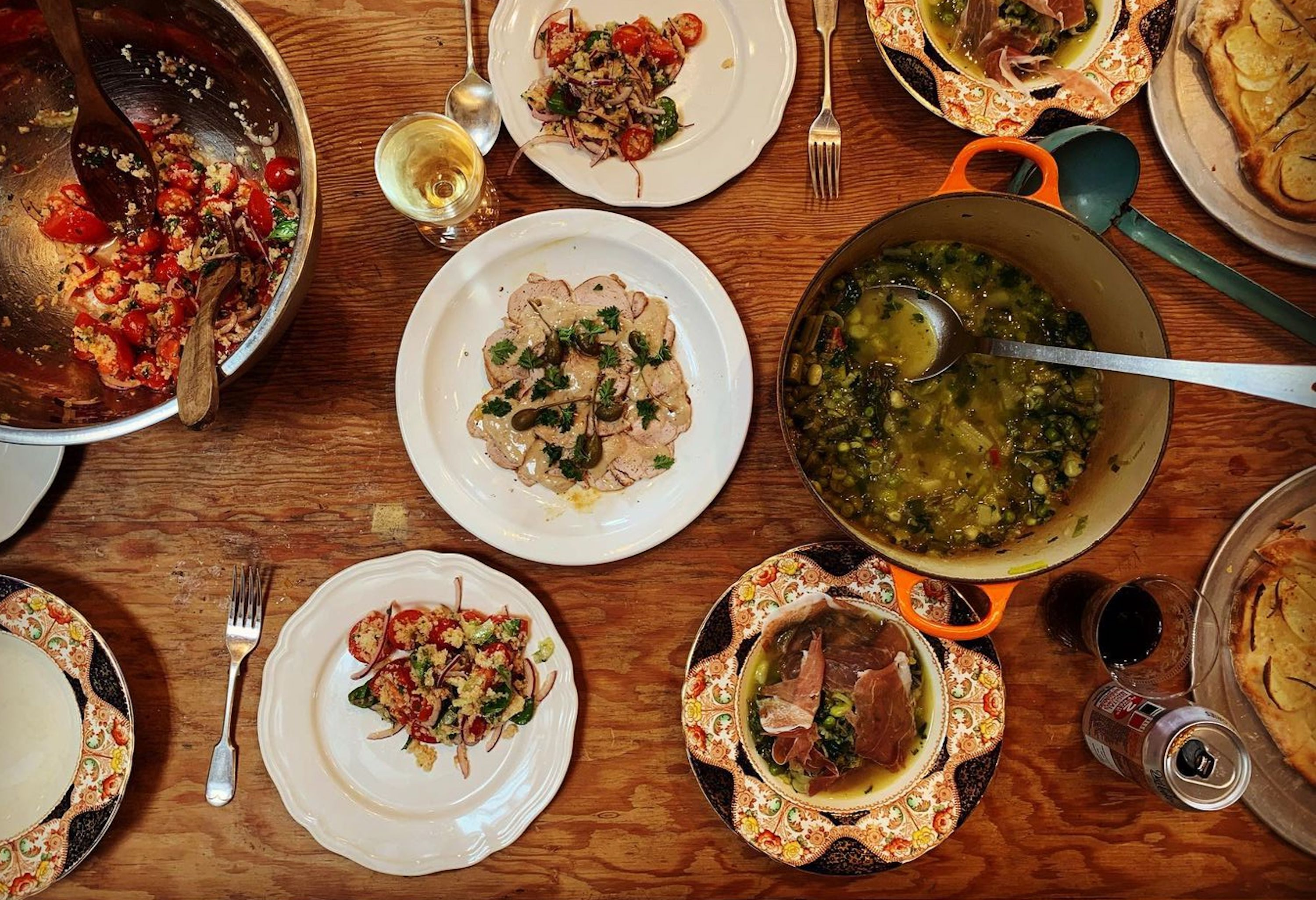 A birdseye view of a wooden dinner table laden with Florentine and Tuscan dishes, including tonnato, peposo, and beans