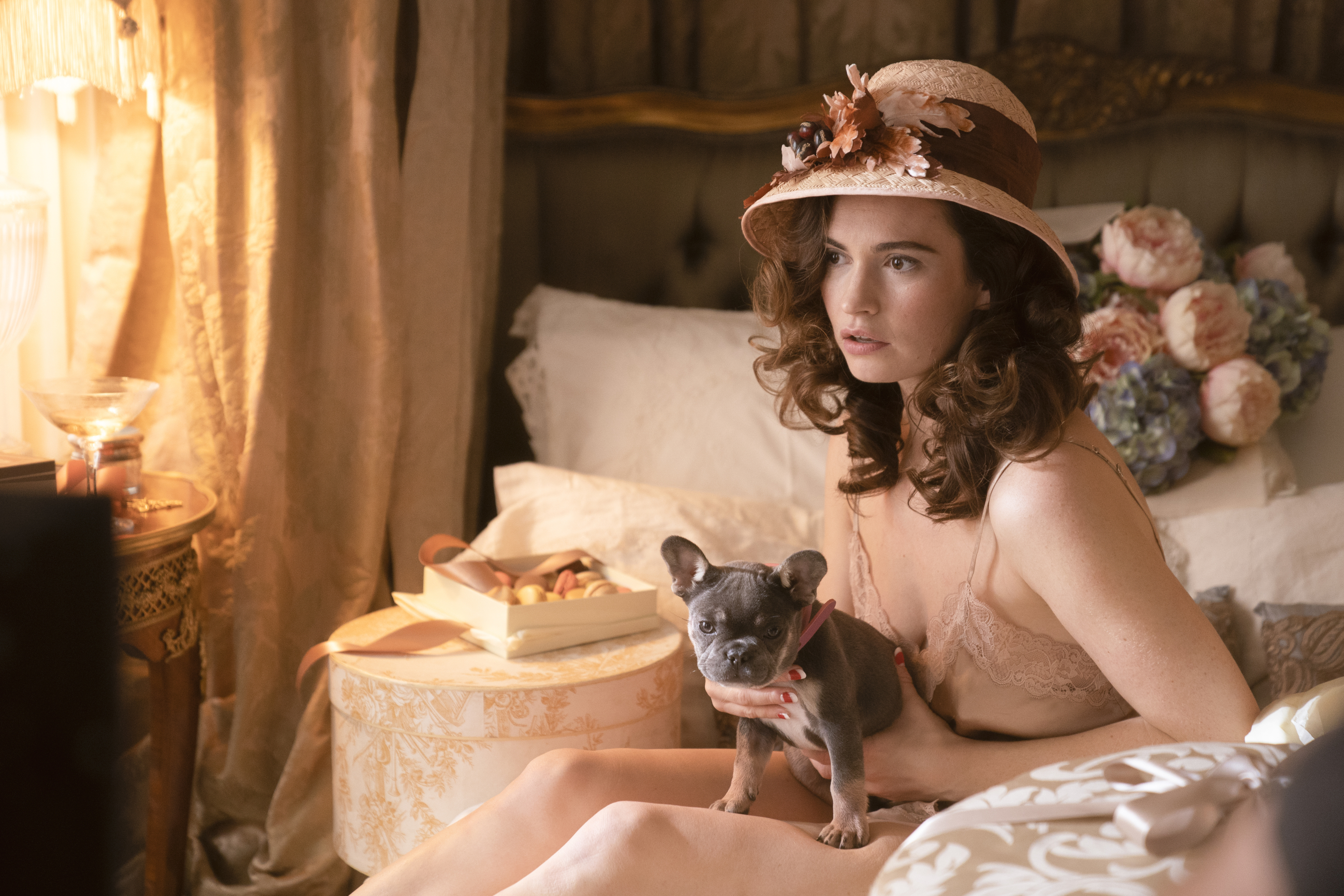 A brunette woman in a lace slip and large cloche hat sits on a bed, holding a lapdog. There's a box of macarons next to her, and a bouquet of peonies and hydrangeas behind her.
