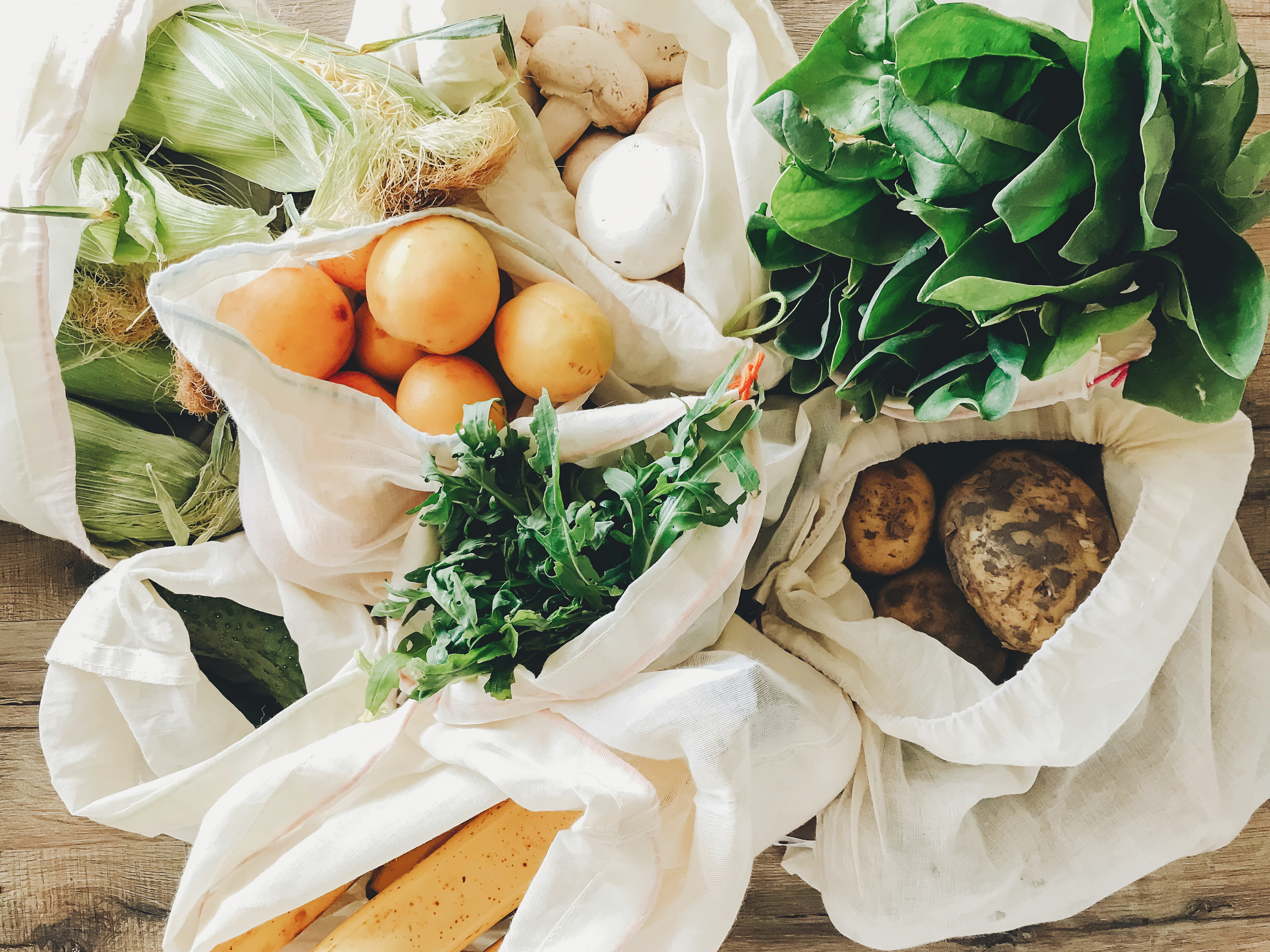 On overhead view of fresh vegetables in cloth bags.