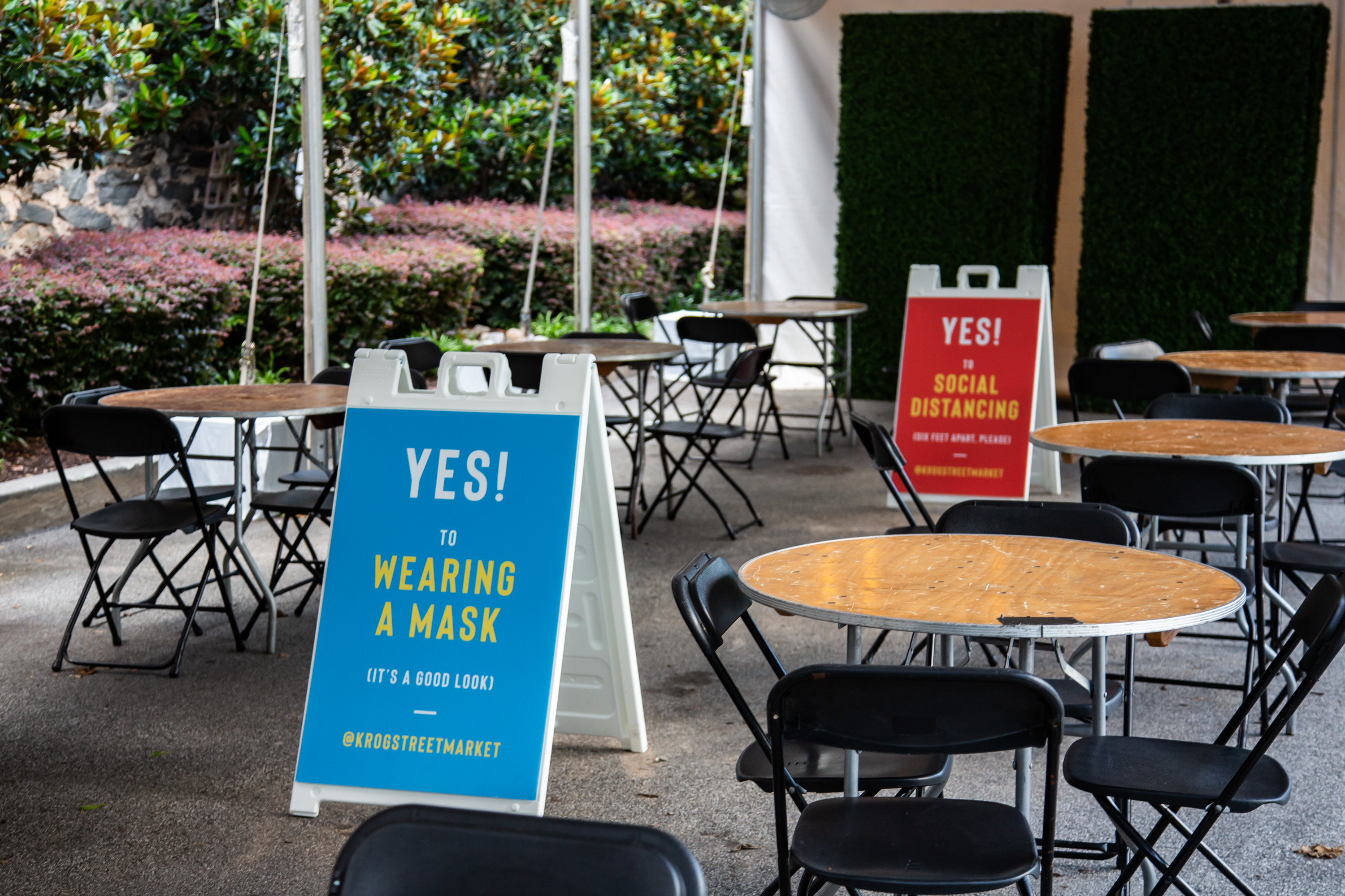 """Blue and red placard signs posted outside of Krog Street Market in Atlanta stating, """"Yes to wearing a Mask"""" inside in June 2020"""
