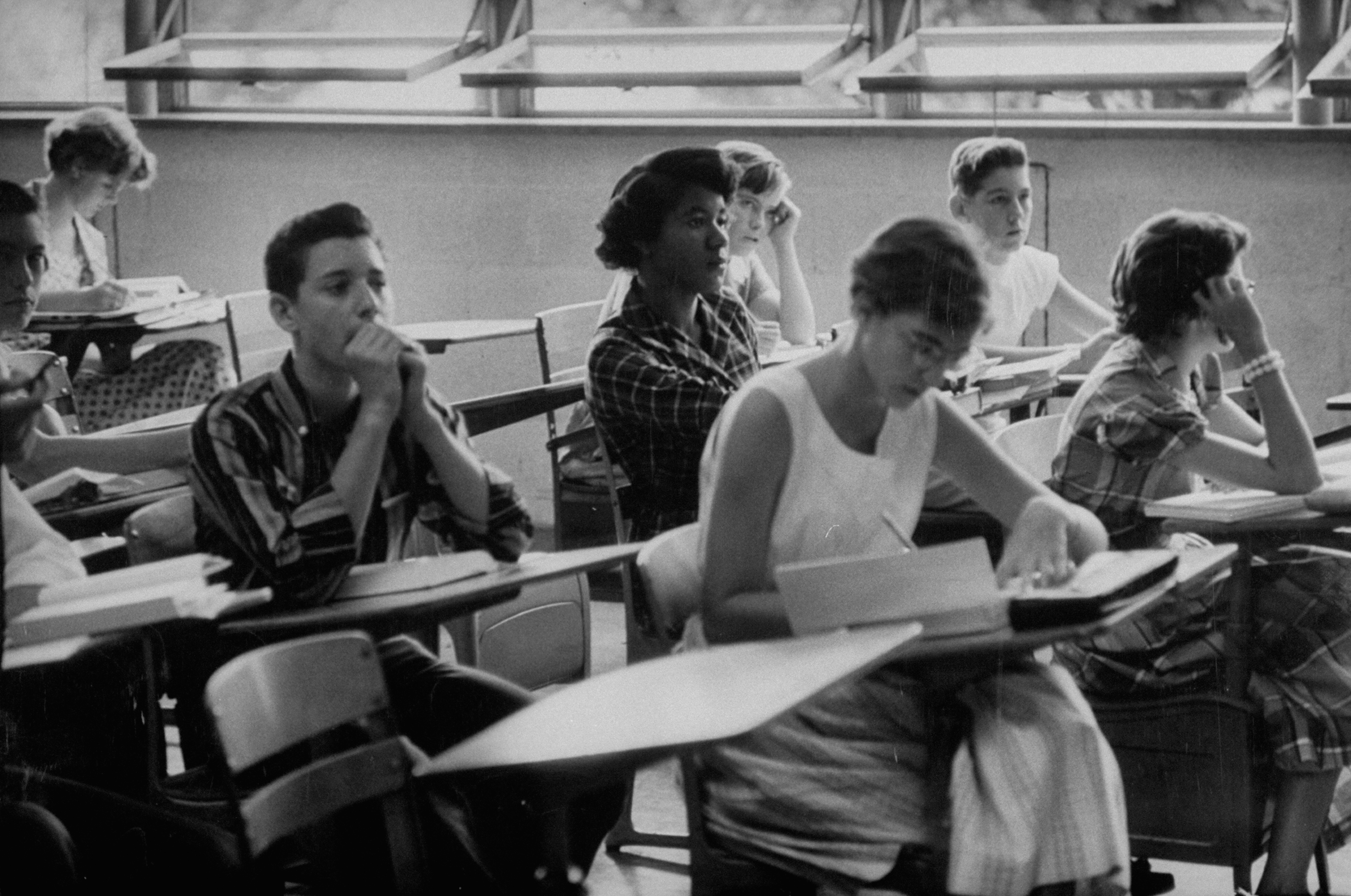 In this historic black and white photograph, one young Black woman sits in the middle of a high school class alongside several white students, after the school was desegregated in Tennessee.