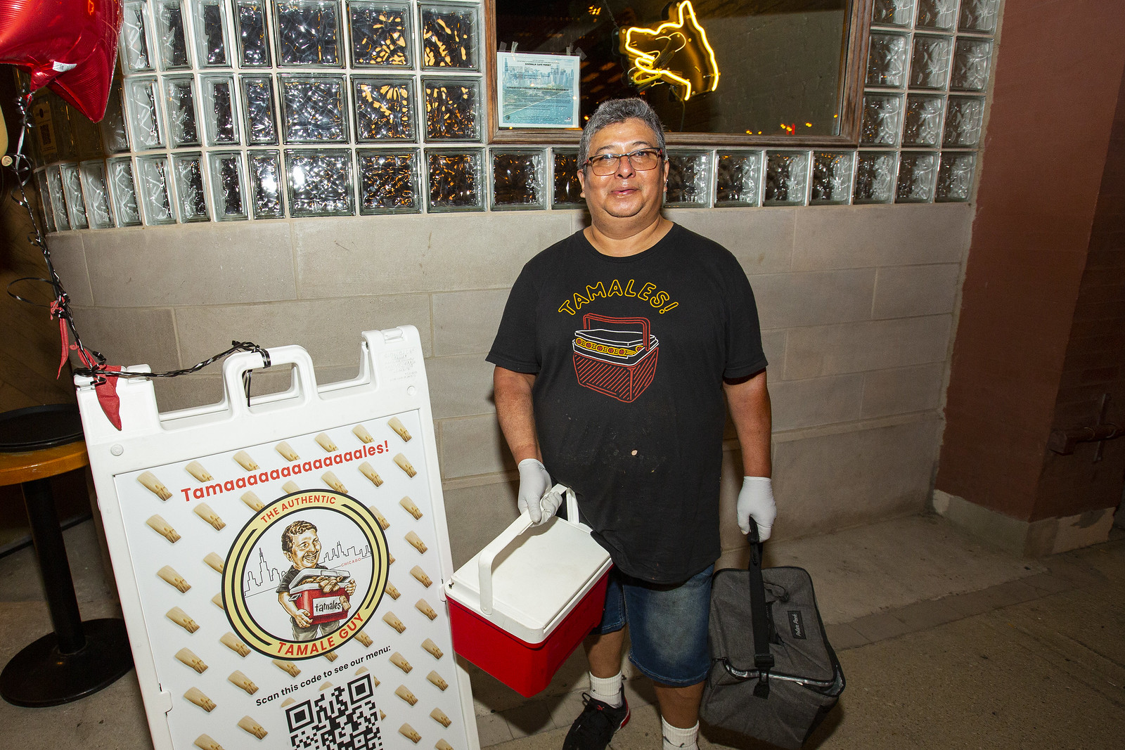 A man holding a red cooler of tamales in black shirt and shorts.