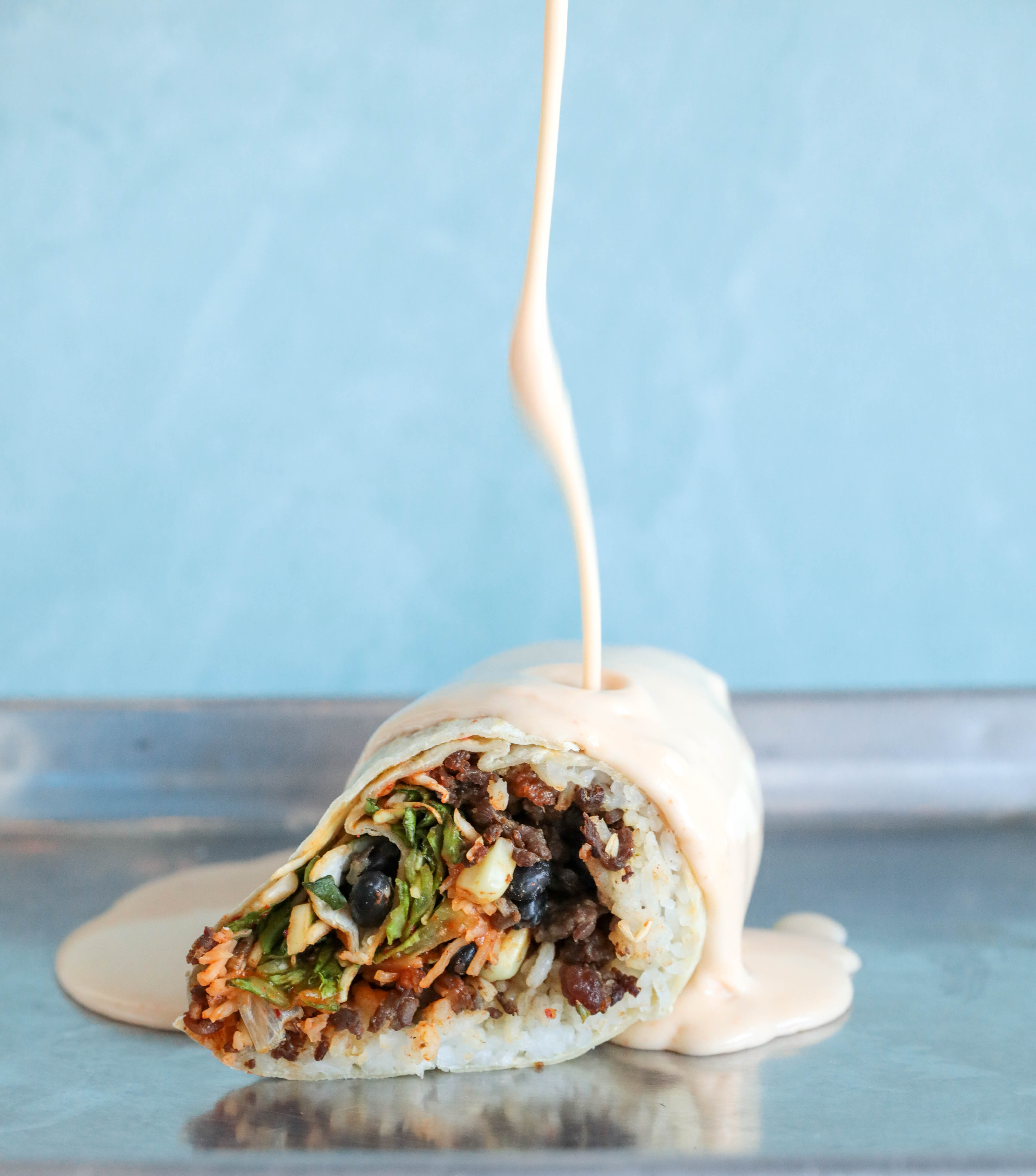 Yellow queso pours down on top of a burrito from Yumbii stuffed with rib-eye, shredded carrots, lettuce, rice and black beans