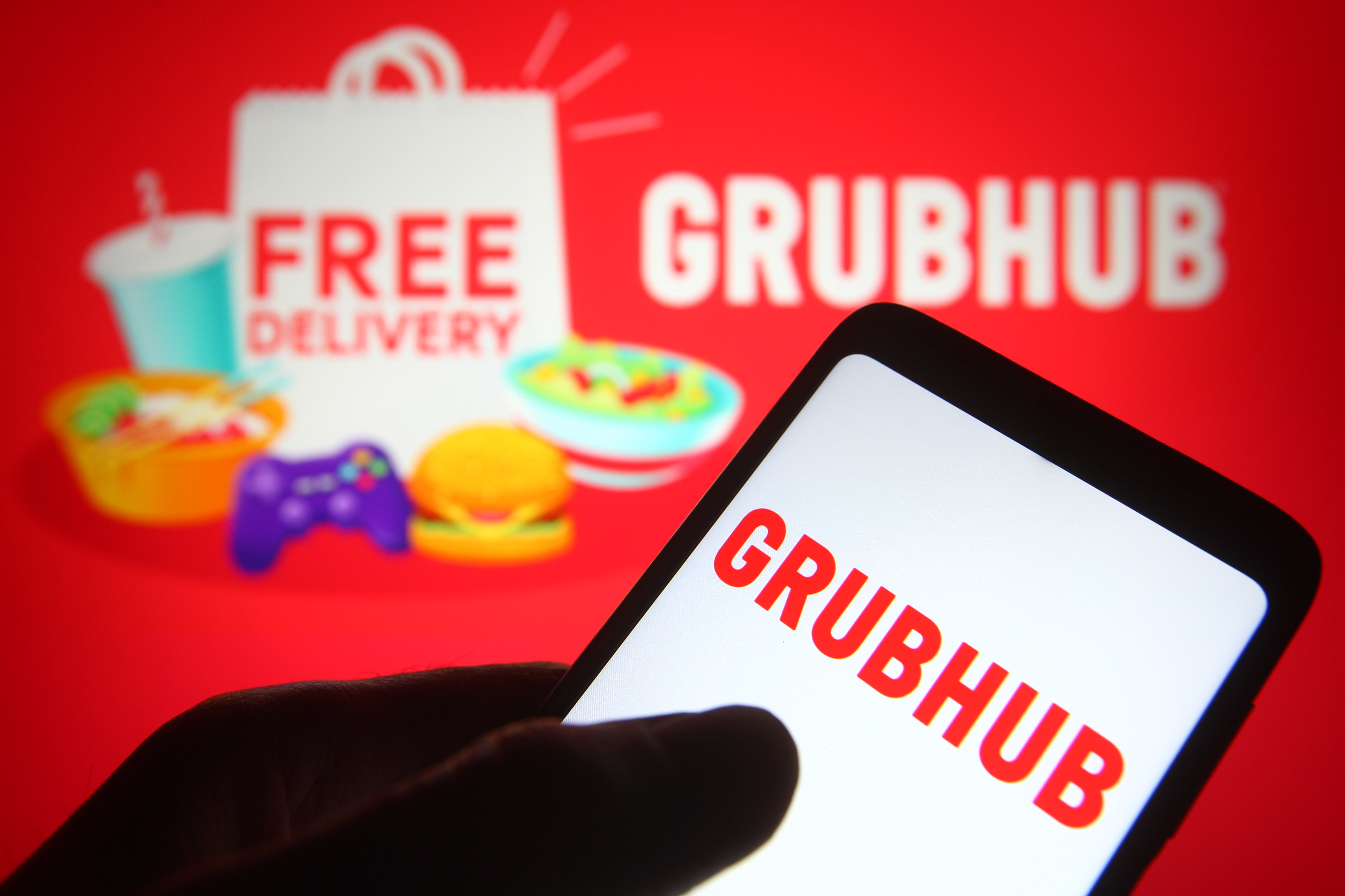 In this photo illustration, a hand swipes on the Grubhub logo on a phone.
