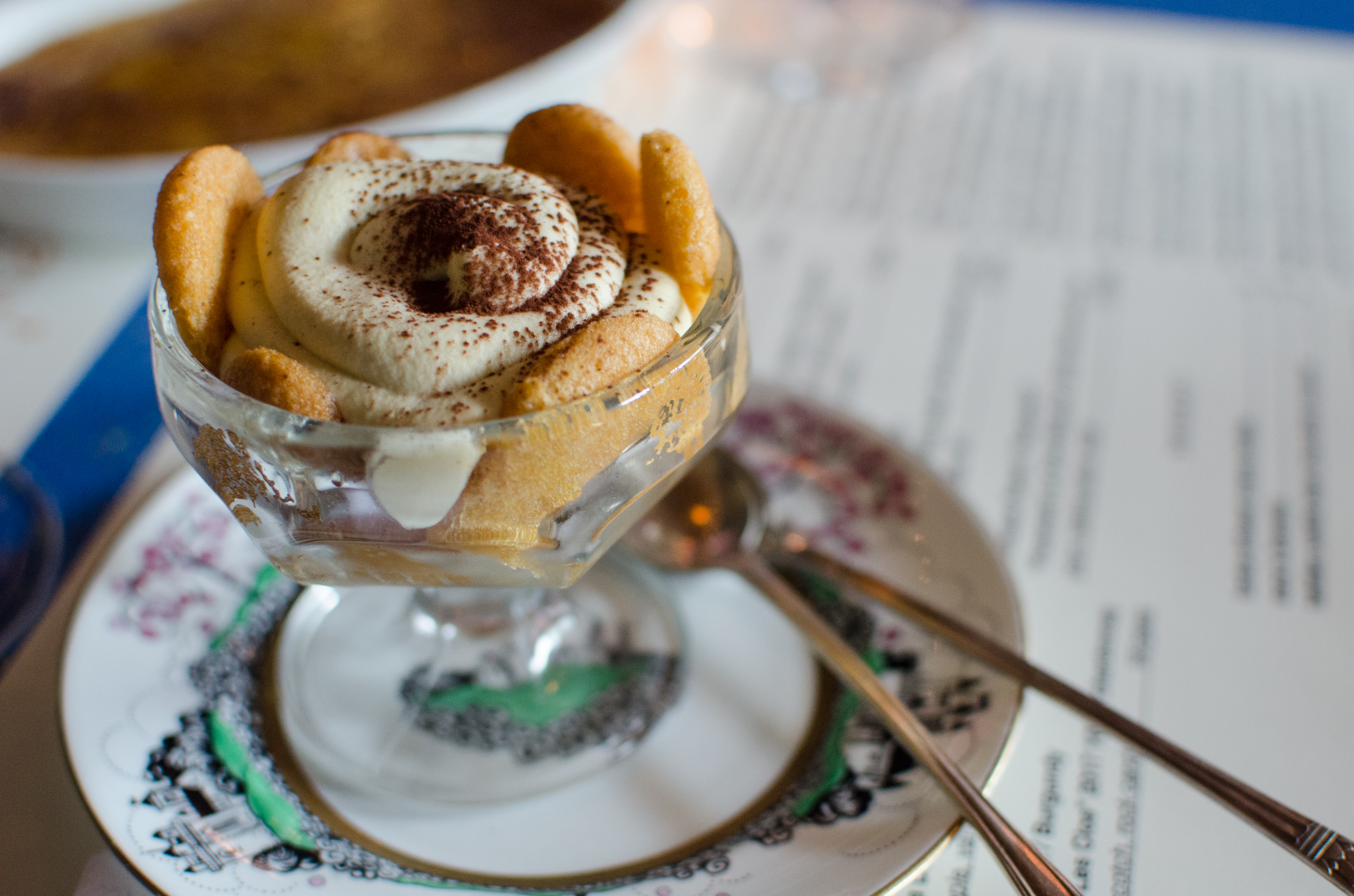 A swirl of tiramisu is in a glass stemmed bowl sitting on a decorative vintage plate. Two long spoons accompany it.