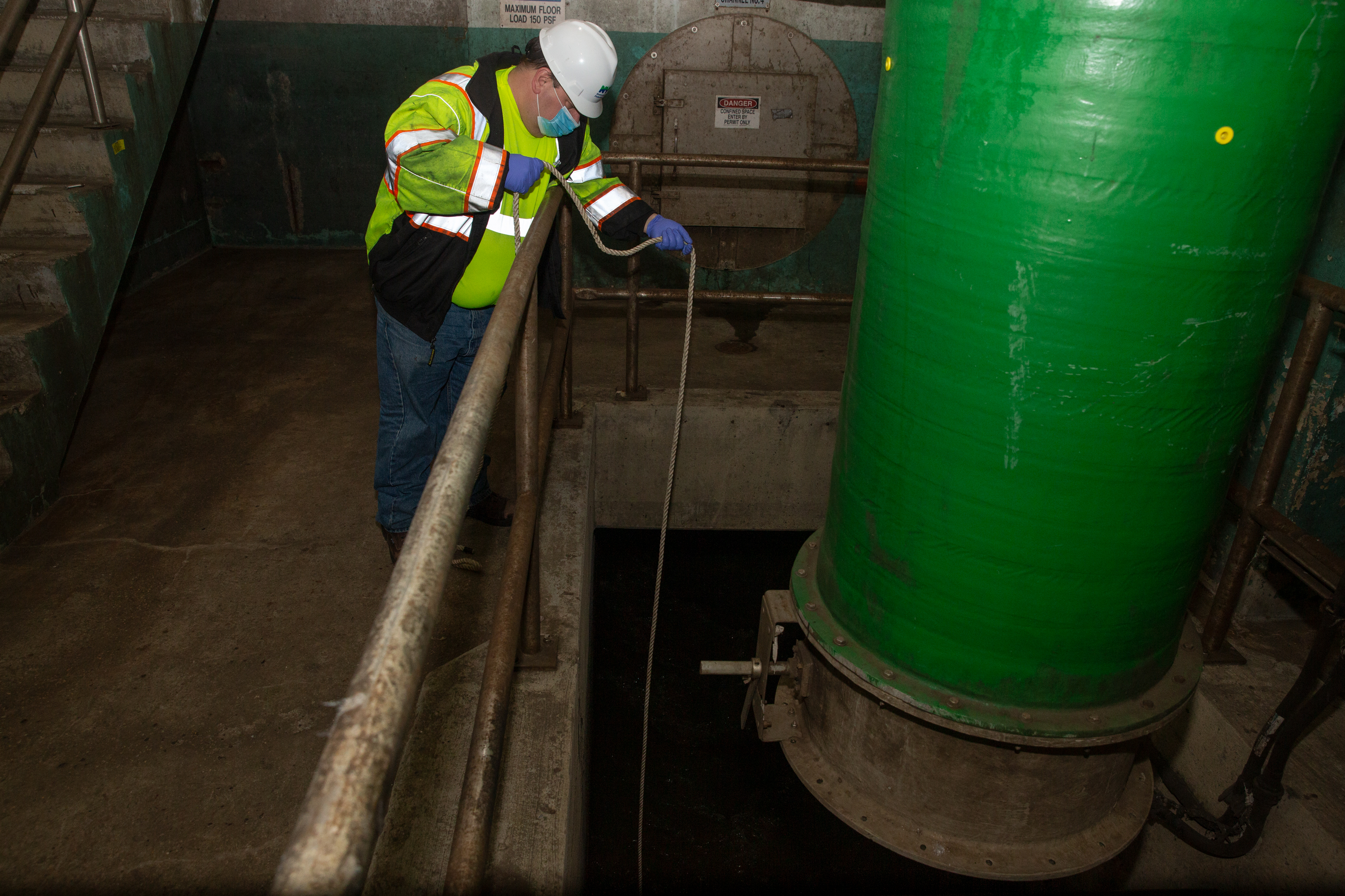 Department of Environmental Protection worker Michael Radano collects a sample from the Newtown Creek Wastewater Treatment Plant for coronavirus sample testing.