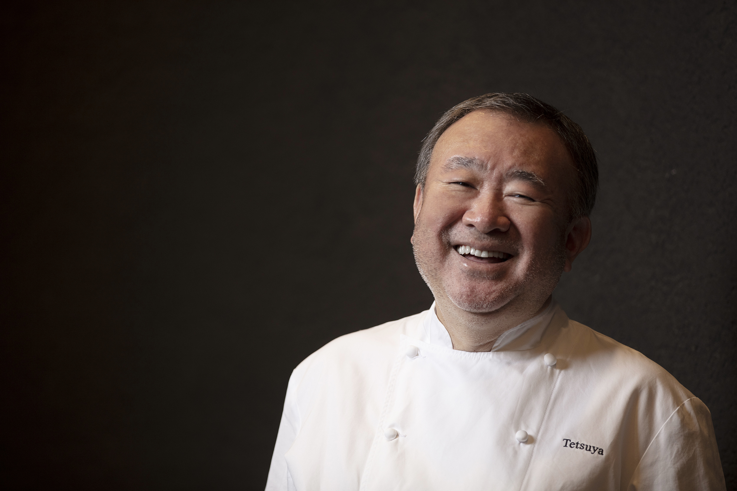 A Japanese man in a white chef's coat