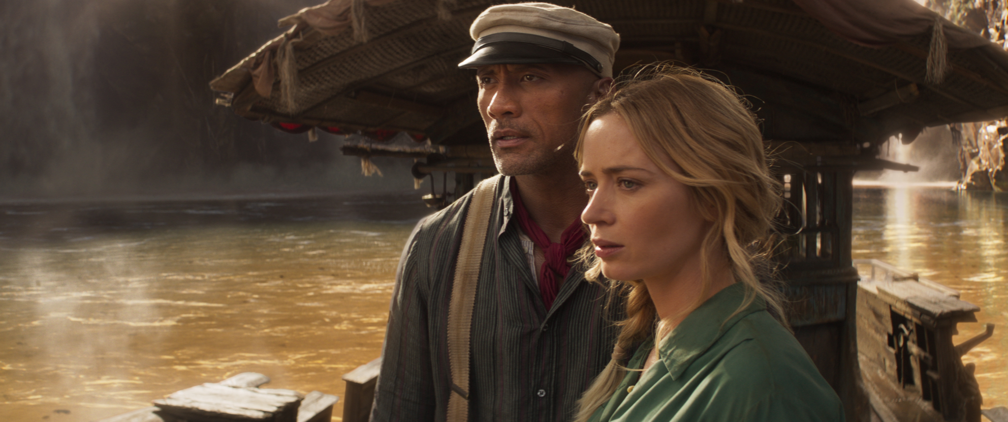 emily blunt as lily and dwayne the rock johnson as frank. they stand on a riverboat, lily slightly in front, blonde hair loose. frank is behind here, a strong, tall man wearing a sailor's hat