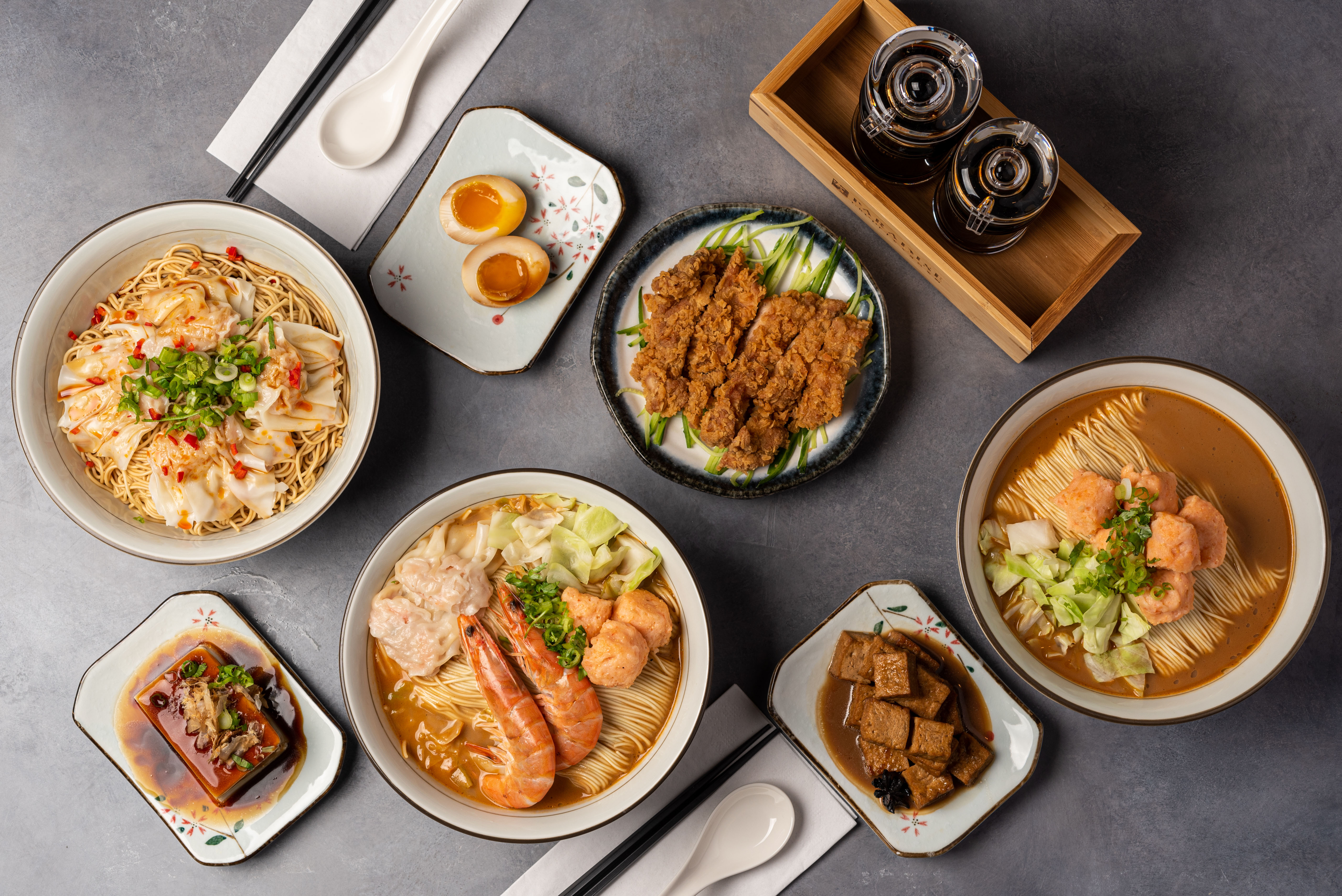 An overhead shot of a table filled with Japanese food, including ramen.