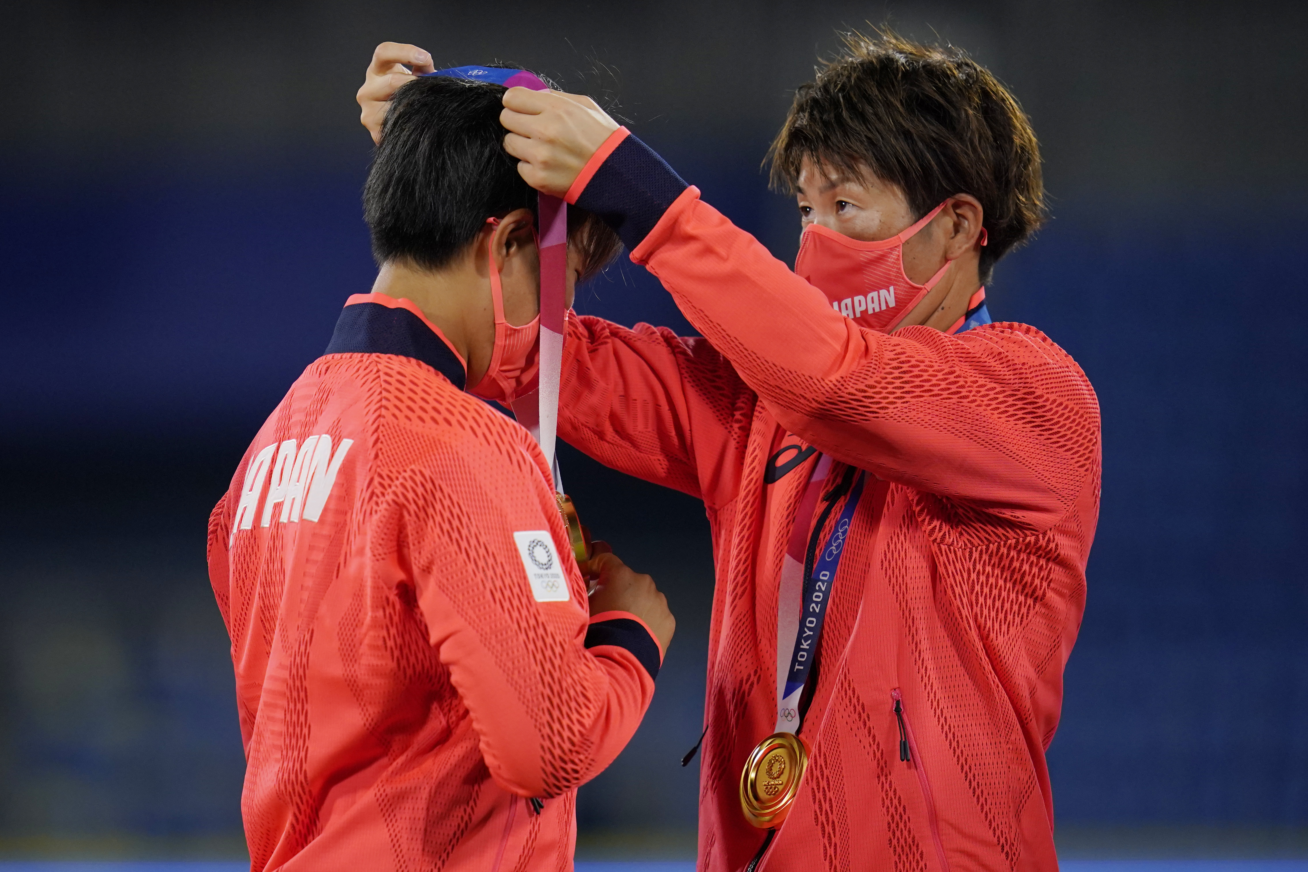 Japan team members adjust their gold medals at the medal ceremony for softball game at the 2020 Summer Olympics.