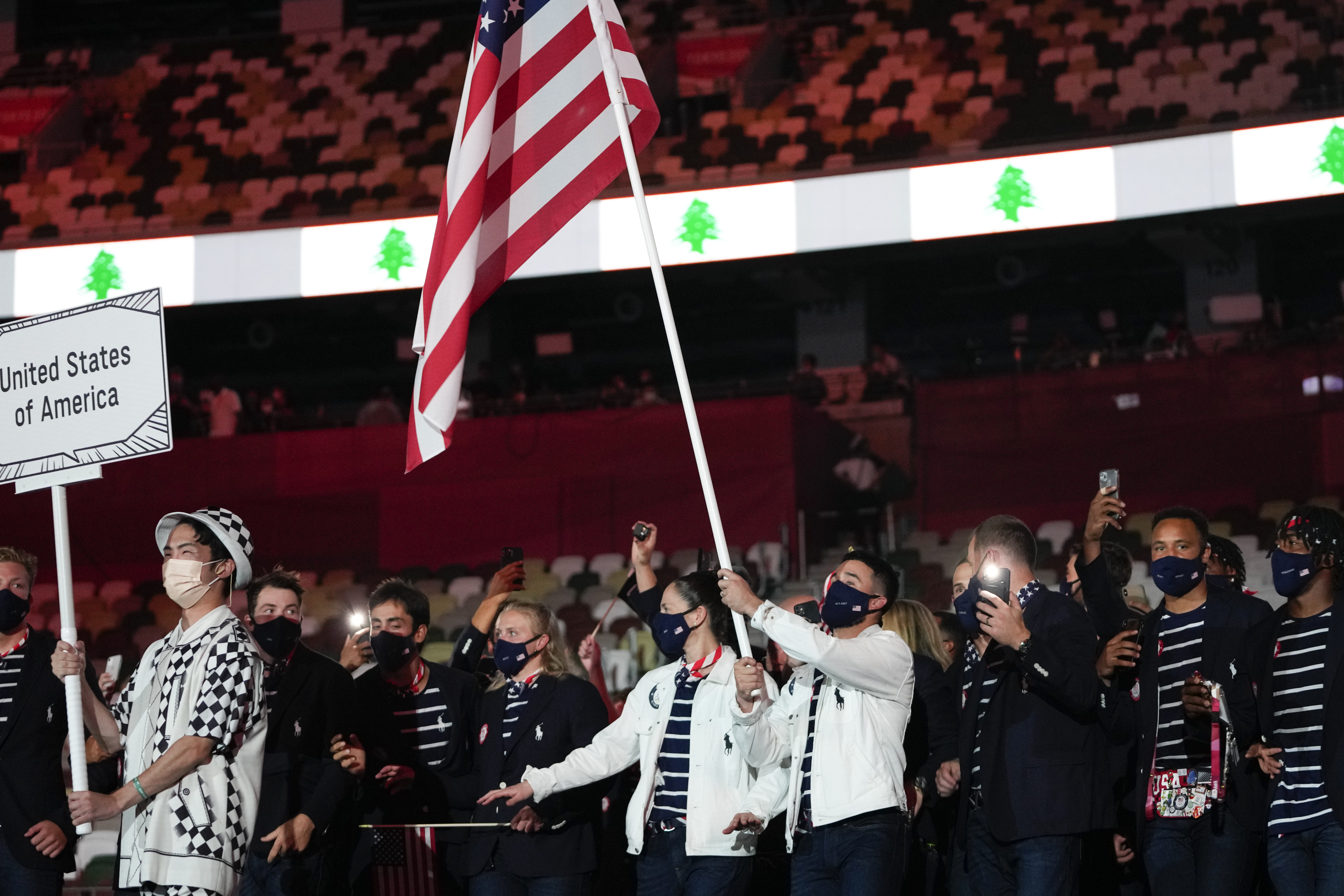 Sue Bird and Eddy Alvarez of the United States carry their country's flag during the opening ceremony at the Summer Olympics.