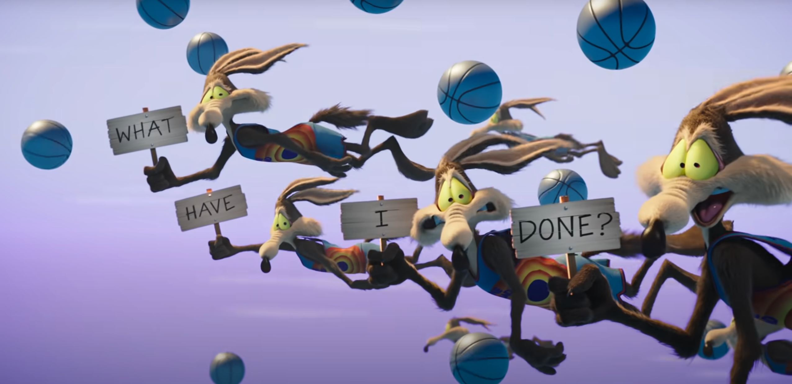 """Several copies of Wile E. Coyote hurdle through the air together, along with several basketballs, holding up signs that say """"What have I done?"""" in this image from Space Jam: A New Legacy"""