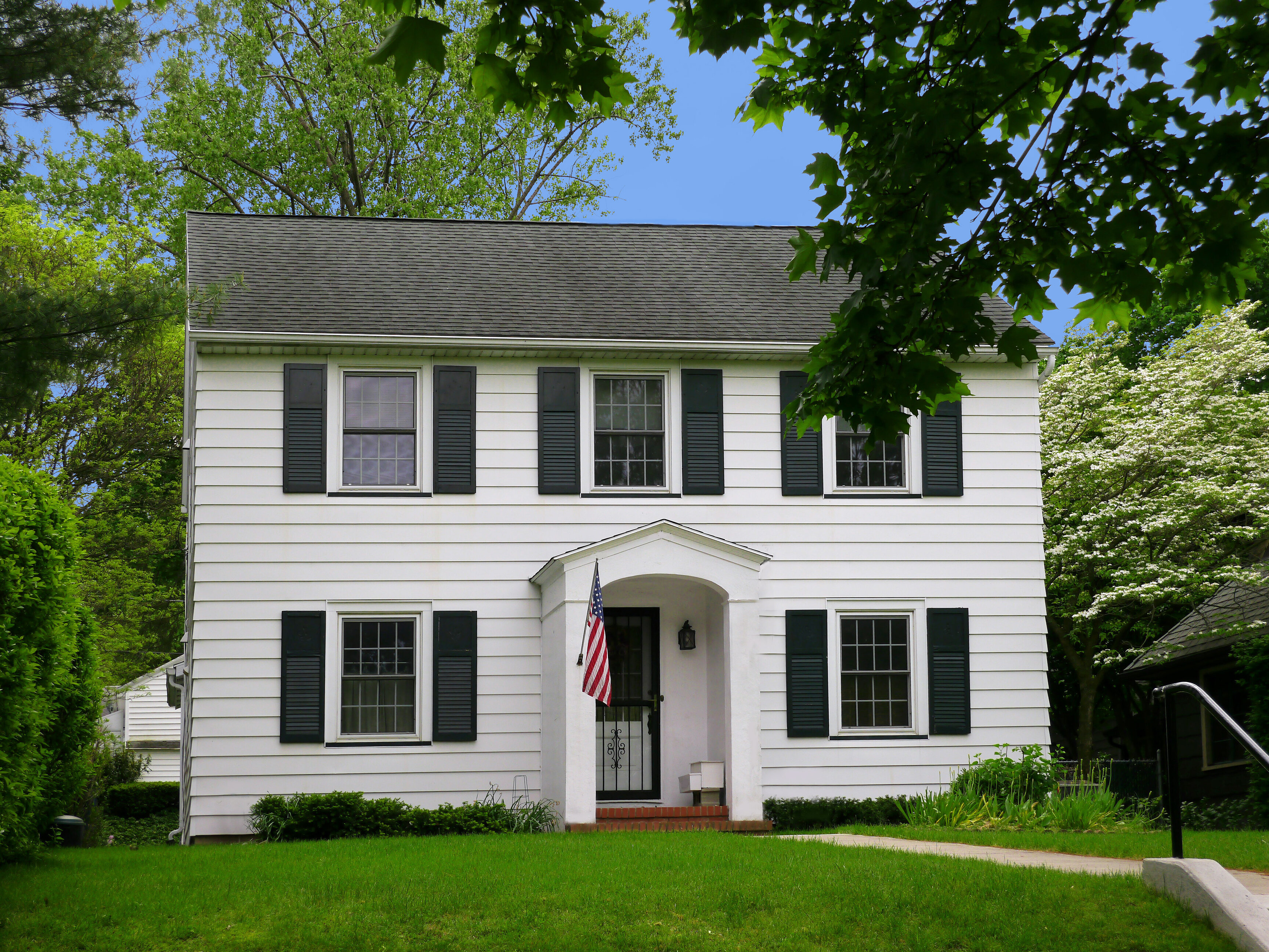 A white colonial house with black shutters, American flag, and large green trees.