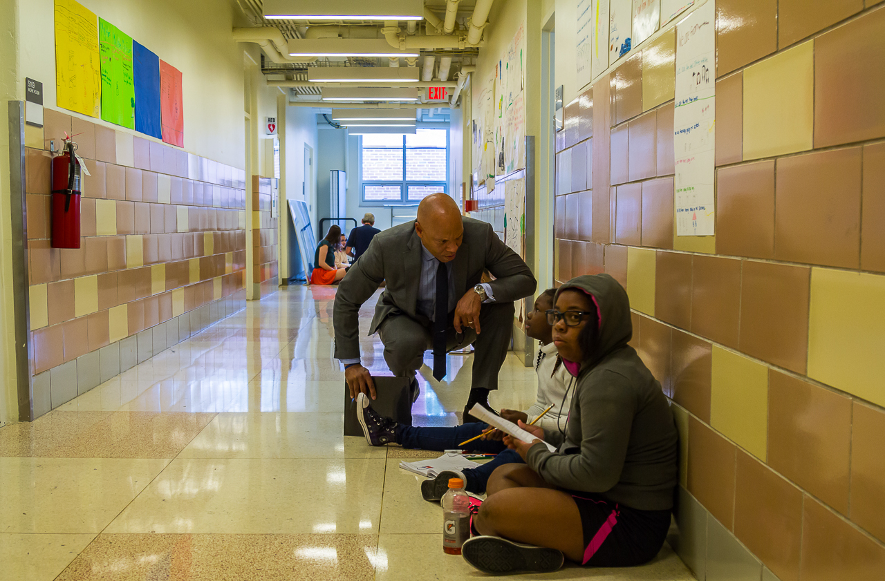 Philadelphia Superintendent William Hite crouches down next to students in a hallway at Science Leadership Academy.