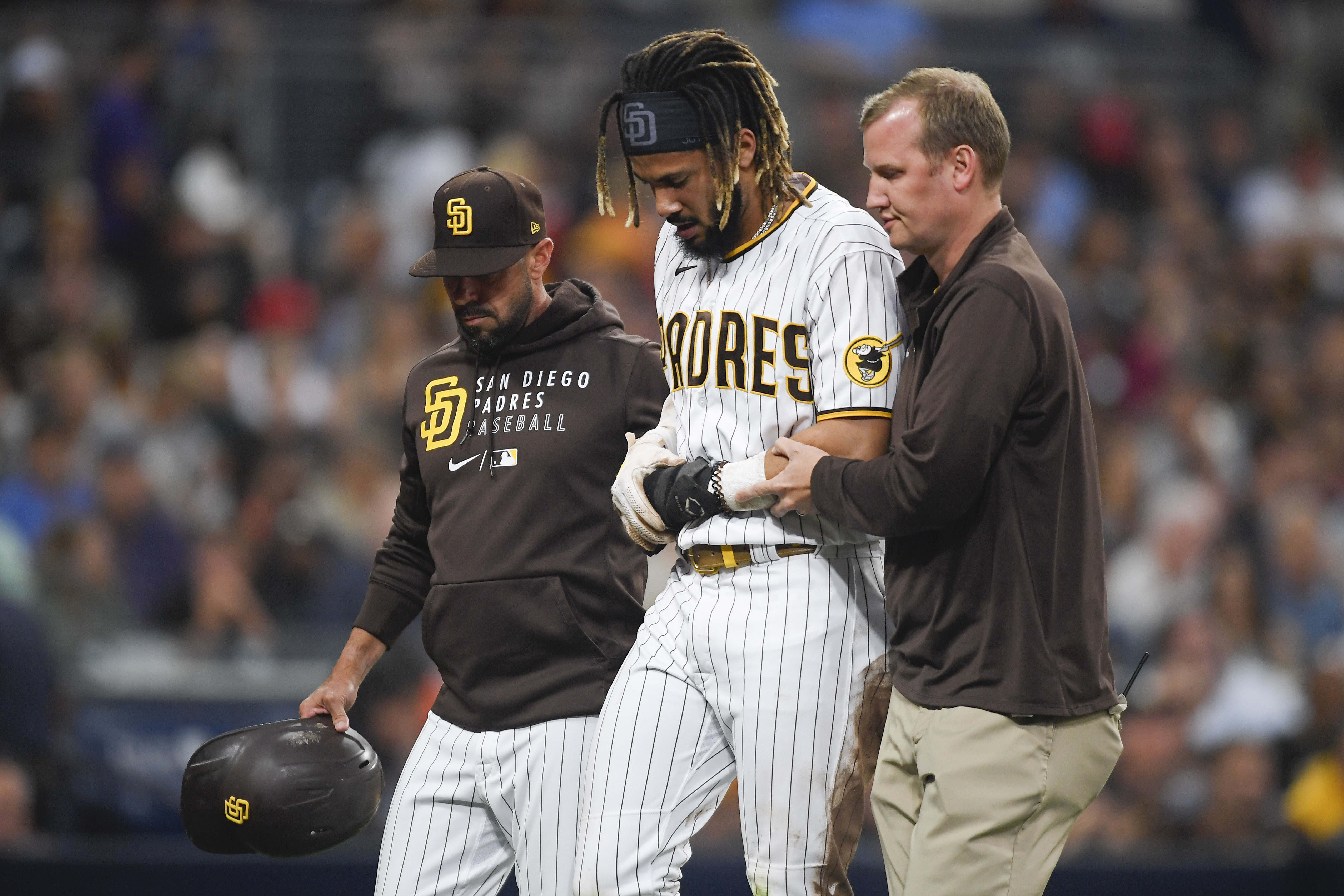 Fernando Tatis Jr. #23 of the San Diego Padres is helped off the field by manager Jayce Tingler and a trainer after he was injured during the first inning of a baseball game against the Colorado Rockies at Petco Park on July 30, 2021 in San Diego, California.