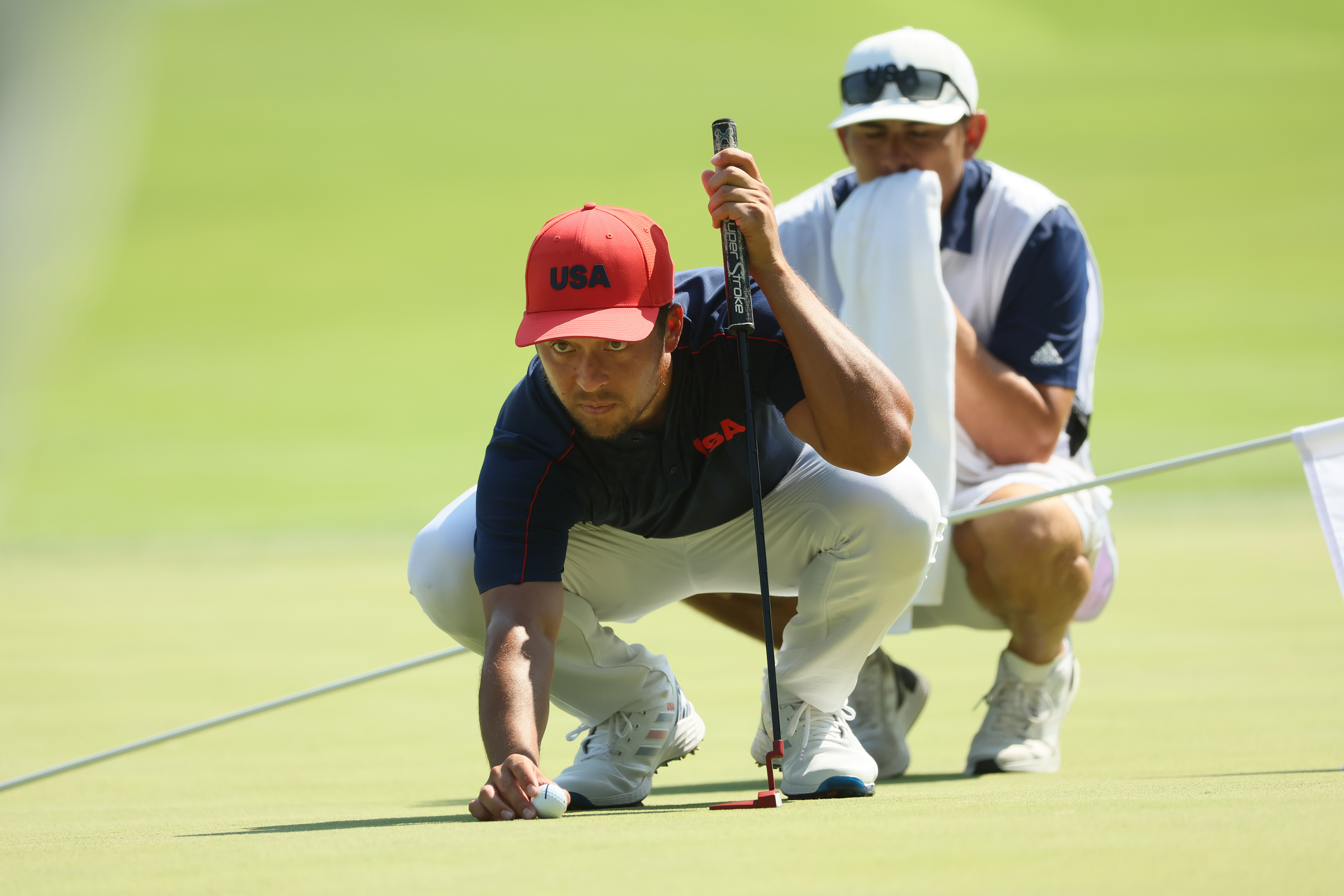 Xander Schauffele of Team United States prepares to putt on the 13th green as caddie Austin Kaiser looks on during the final round of the Men's Individual Stroke Play on day nine of the Tokyo 2020 Olympic Games at Kasumigaseki Country Club on August 01, 2021 in Kawagoe, Saitama, Japan.