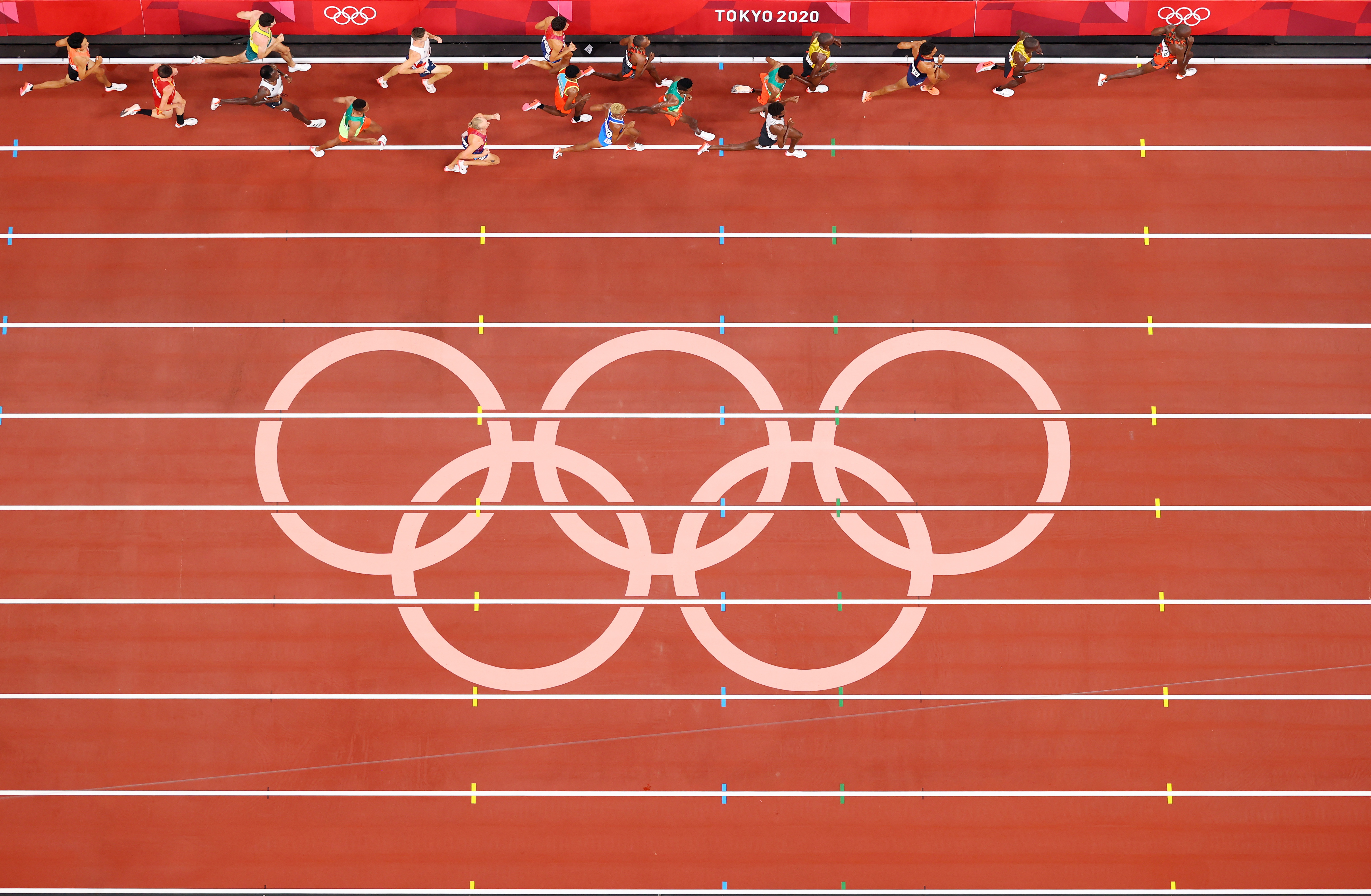 The Olympic rings on a track and field track seen from high above, with competitors running in the inside lane.