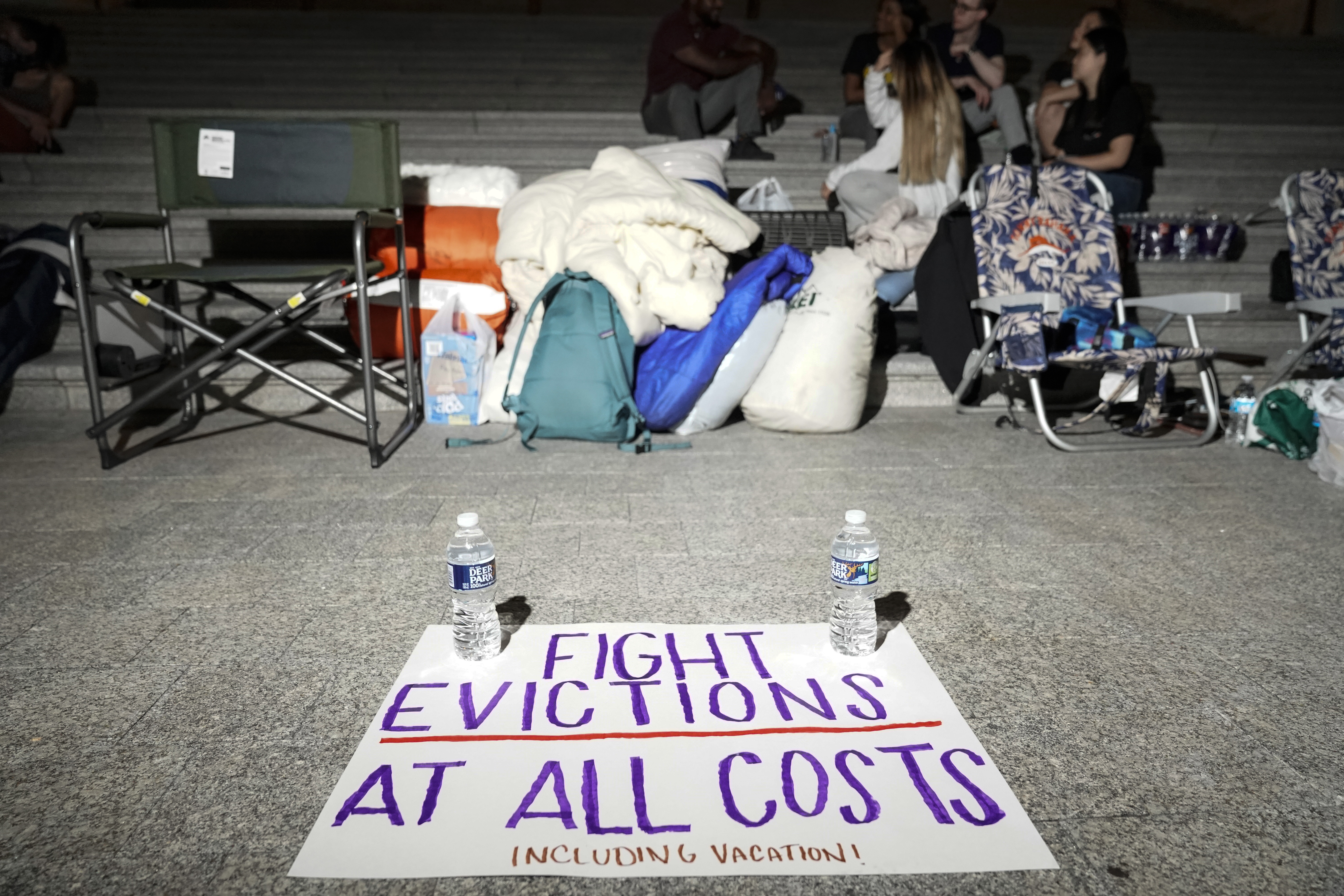 A sign calling for fighting evictions is set on the ground in front of outdoors chairs, bags and water bottles, where people have been camping outside.