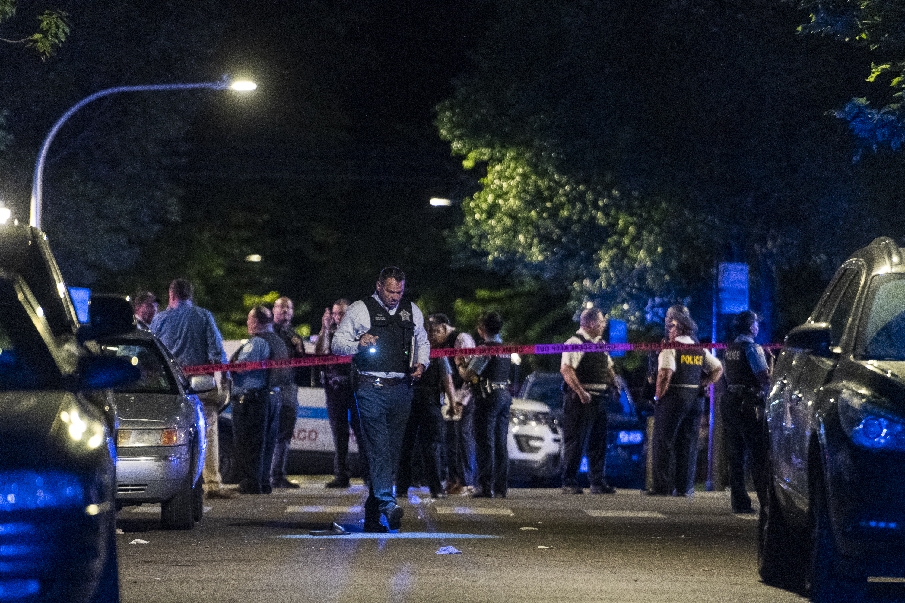 Chicago police work the scene where at least 8 people were shot in the 6300 block of South Artesian Ave in the Marquette Park neighborhood, Sunday, June 27, 2021.