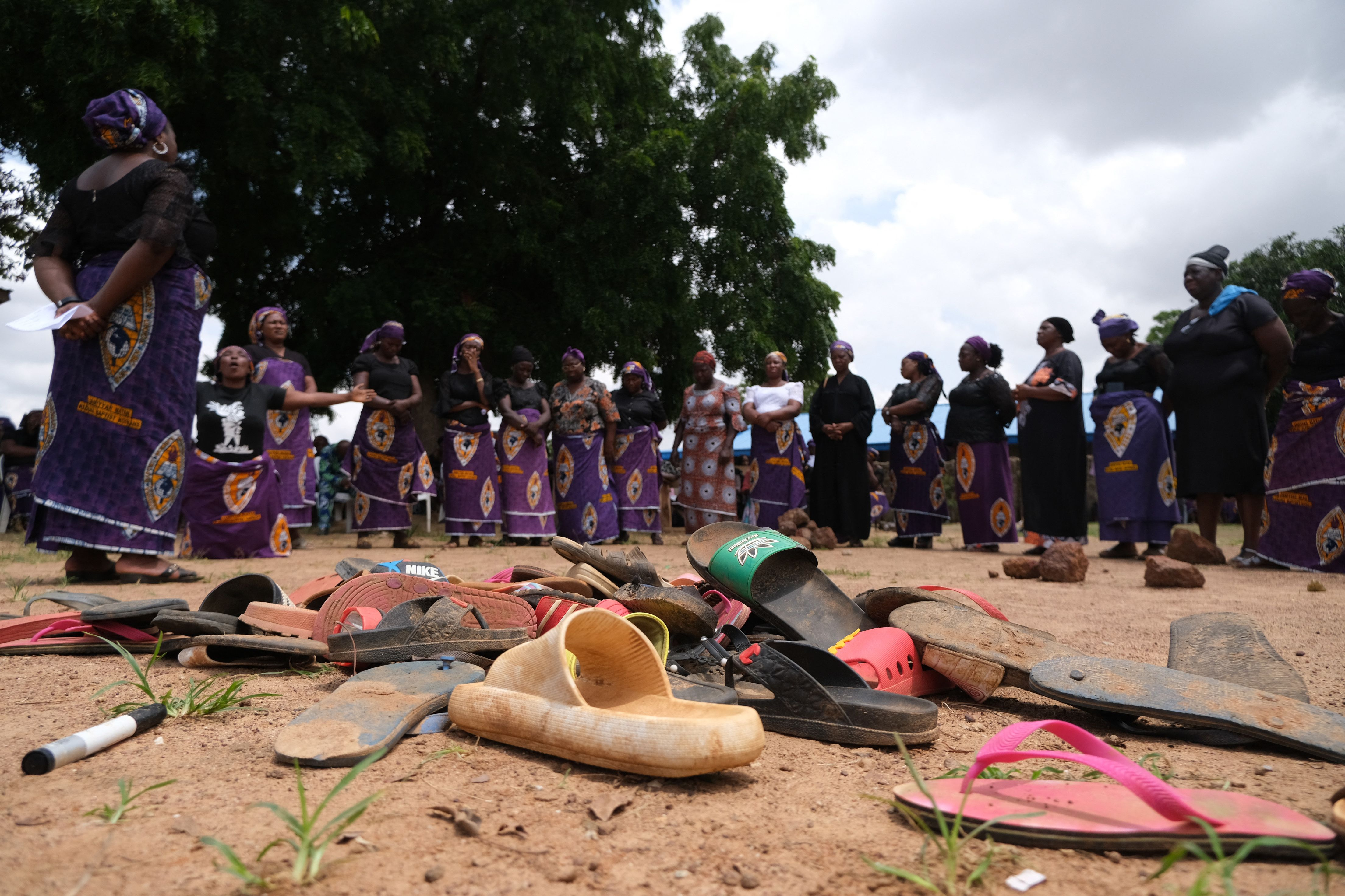 Flip flops from students of Bethel Baptist High School are pictured inside the school premises. In the background, parents of abducted students pray for the return of their children abducted by gunmen in the Kaduna state, northwest Nigeria, on July 14, 2021.