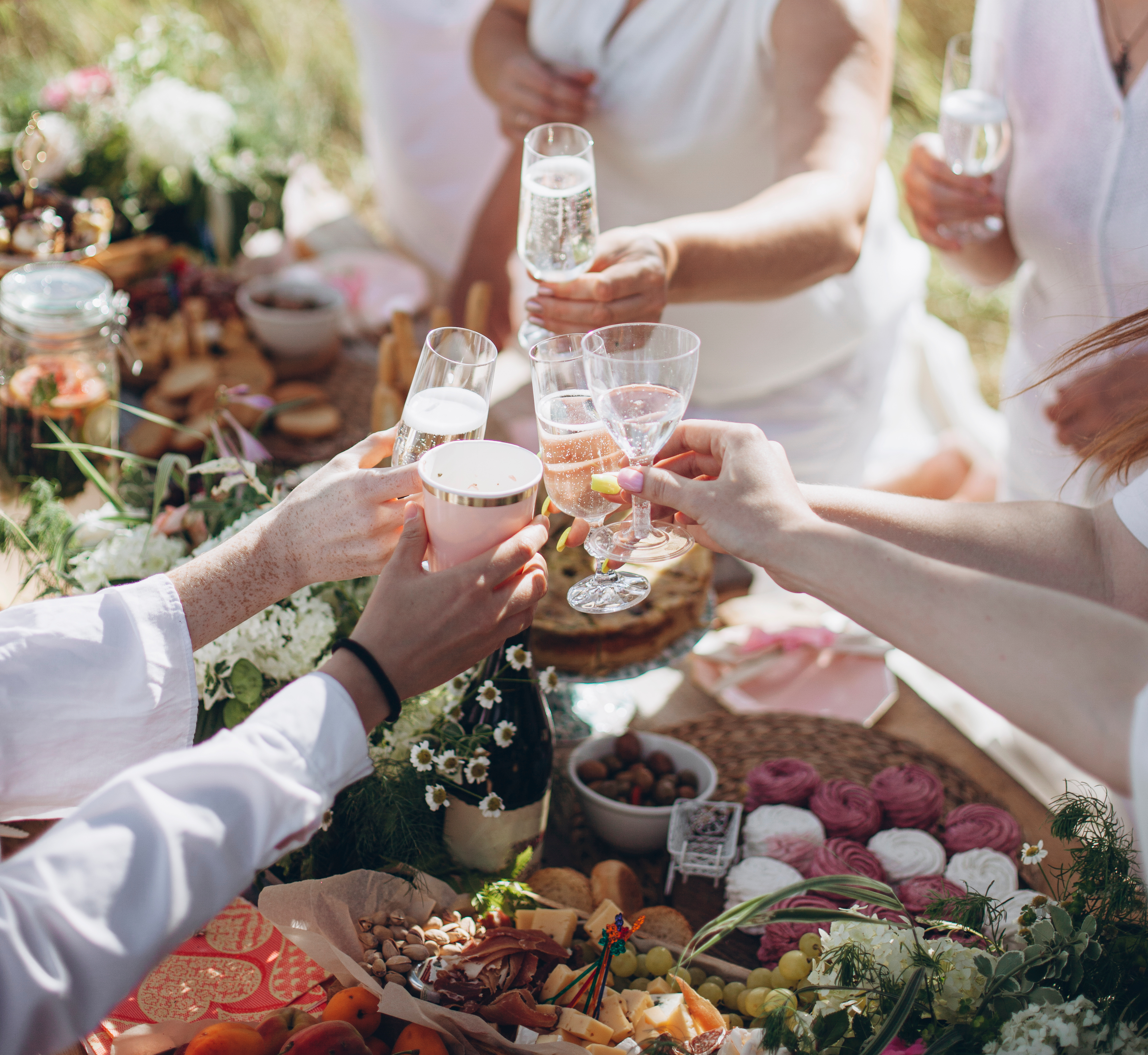 Hands of people wearing white around a picnic table toast with bubbly in glasses.