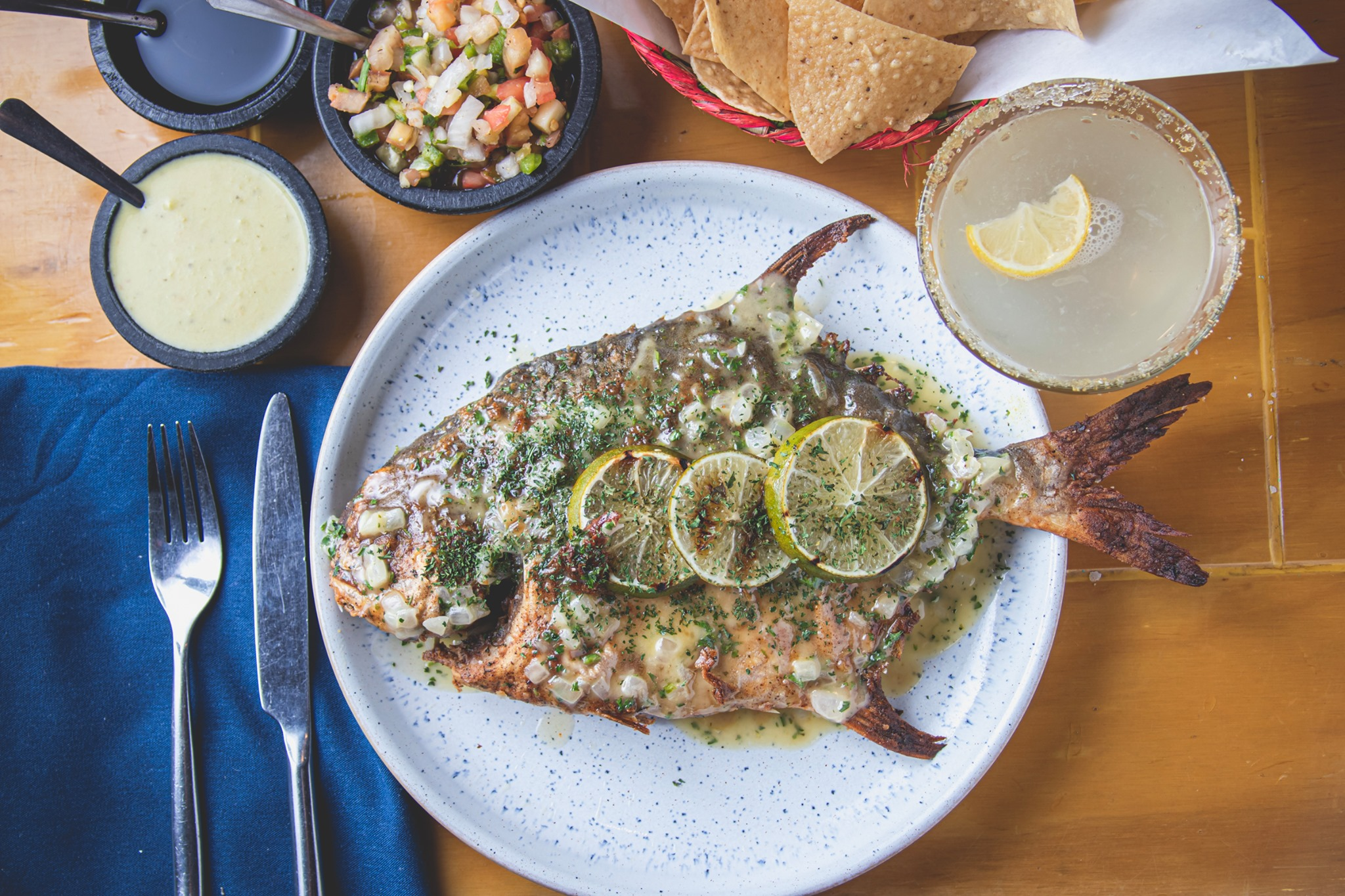 a overhead shot of a whole roasted pompano fish topped with lime slices and flanked by a margarita and various sauces