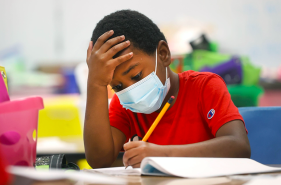 A young boy wearing a red shirt and a mask writes in a packet at his desk.