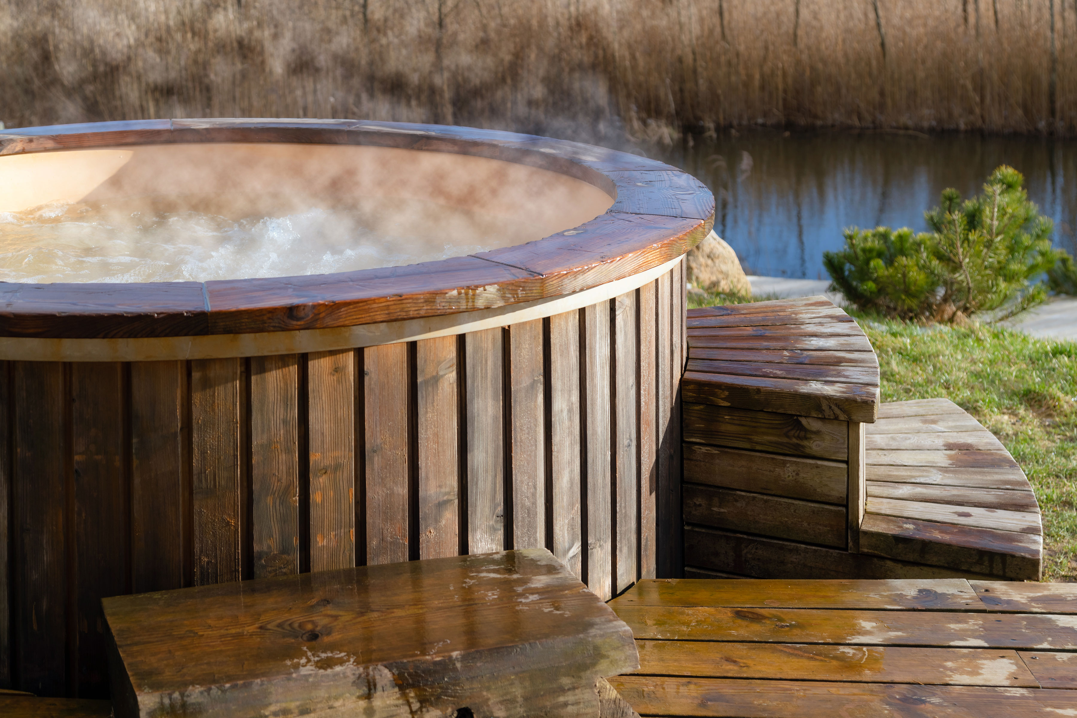 A round, wooden hot tub bubbles and steams next to a wet deck.