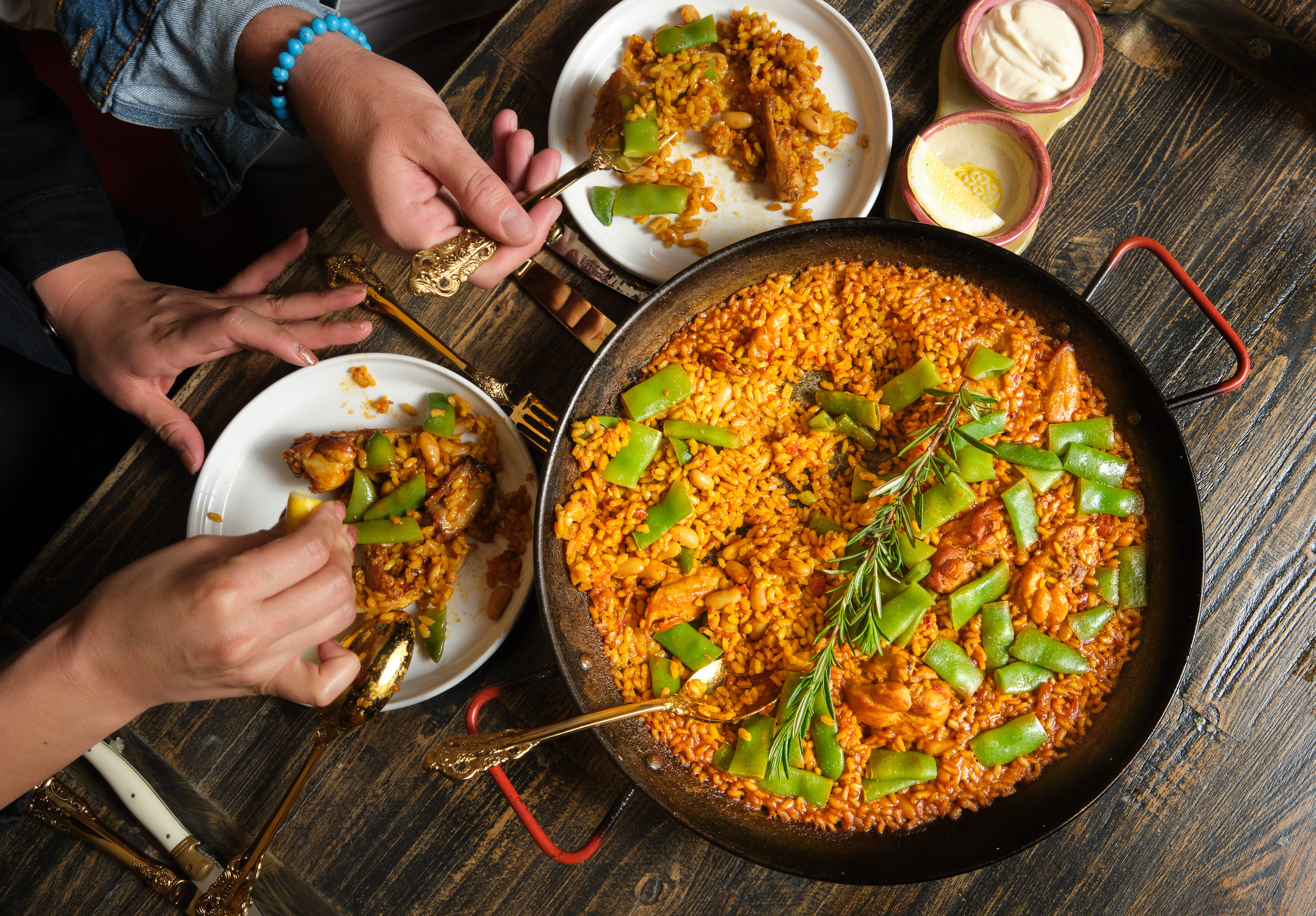 A pan of paella with hands in the photo
