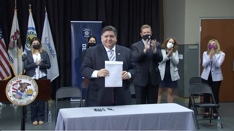Gov. J.B. Pritzker holds up new gun reform legislation signed into law Monday.