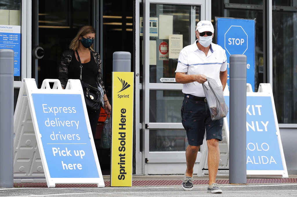 Shoppers wear face masks as they leave a Walmart store in Vernon Hills, Ill.