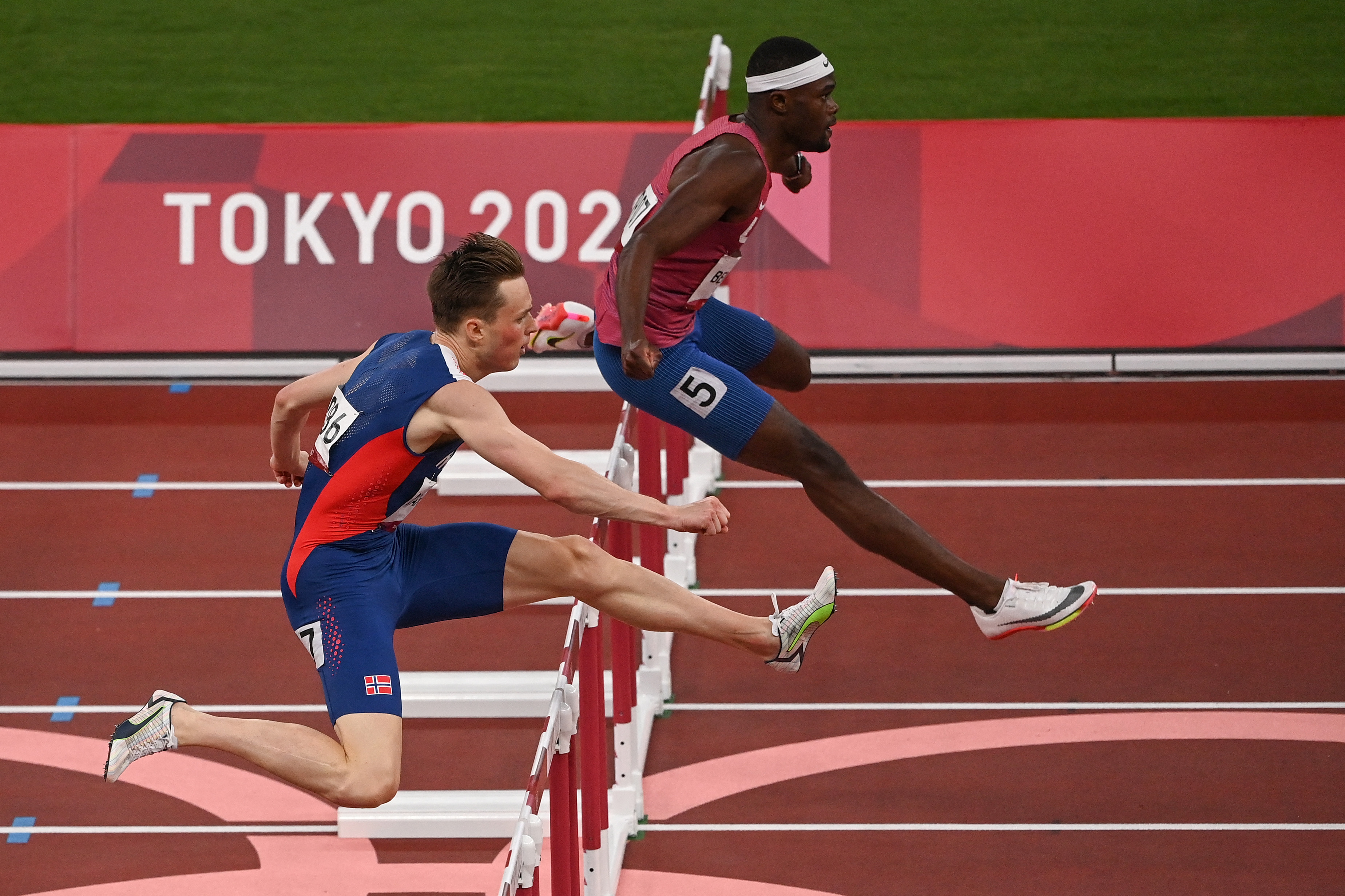 Norway's Karsten Warholm and USA's Rai Benjamin compete in the men's 400m hurdles semi-finals during the Tokyo 2020 Olympic Games at the Olympic stadium in Tokyo on August 1, 2021.
