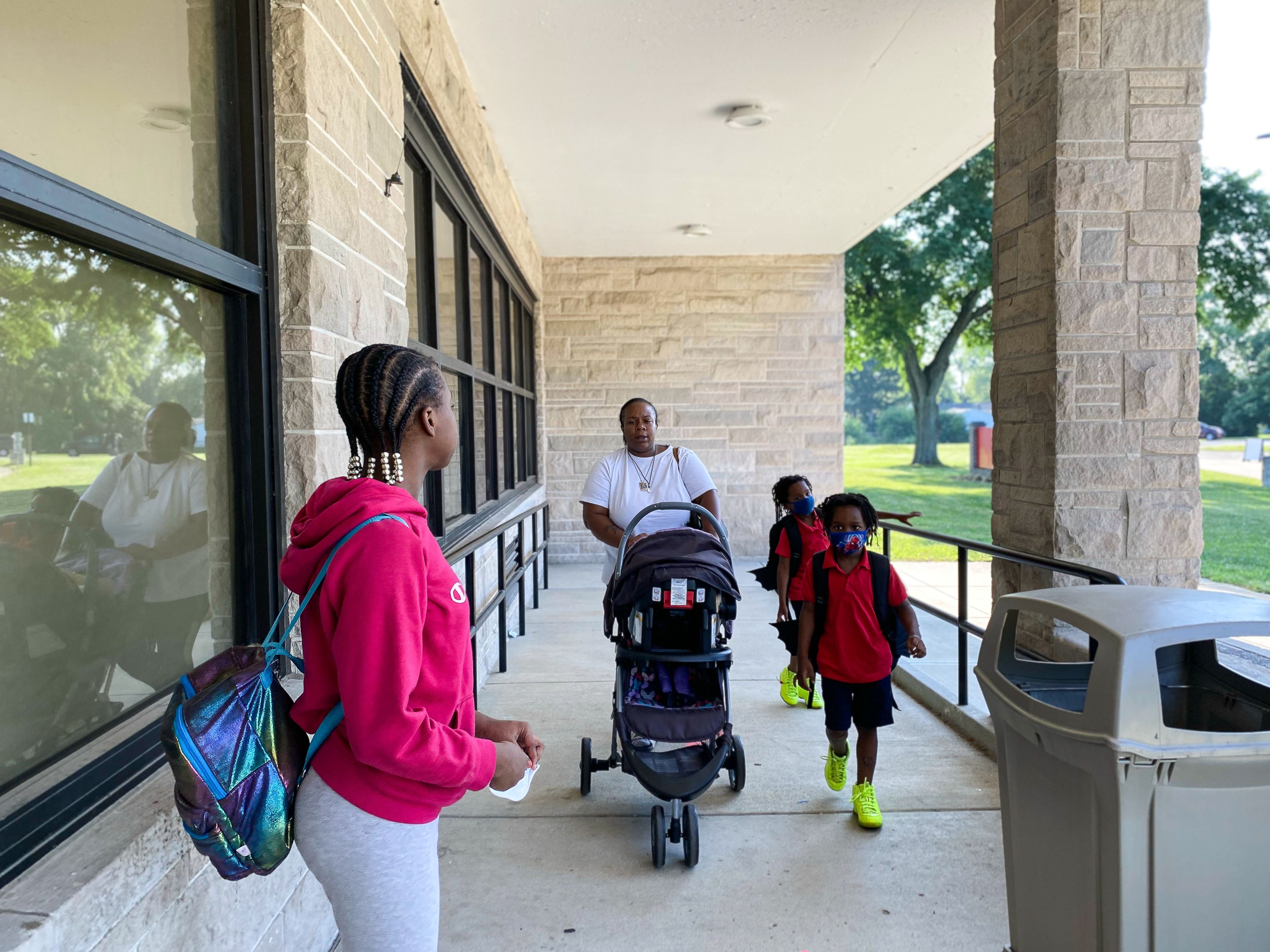 A parent walks pushing a stroller walks up a school ramp with two of her first graders and an older student wearing a backpack.