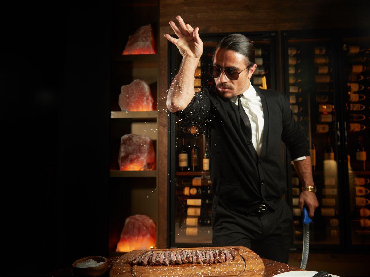 Salt Bae in a suit, sprinkling salt over a steak on a wooden board