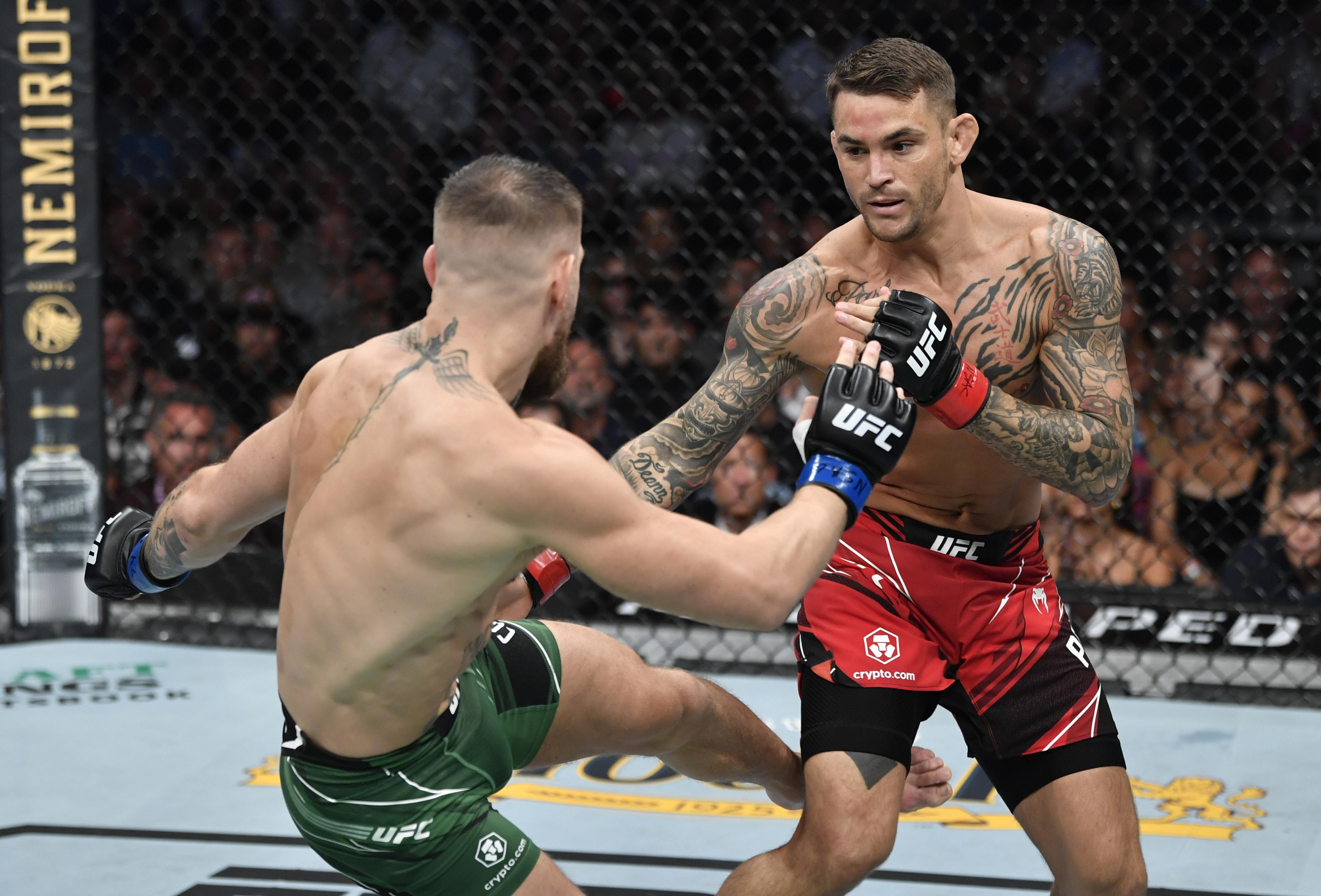Dustin Poirier absorbs one of Conor McGregor's leg kicks at UFC 264.