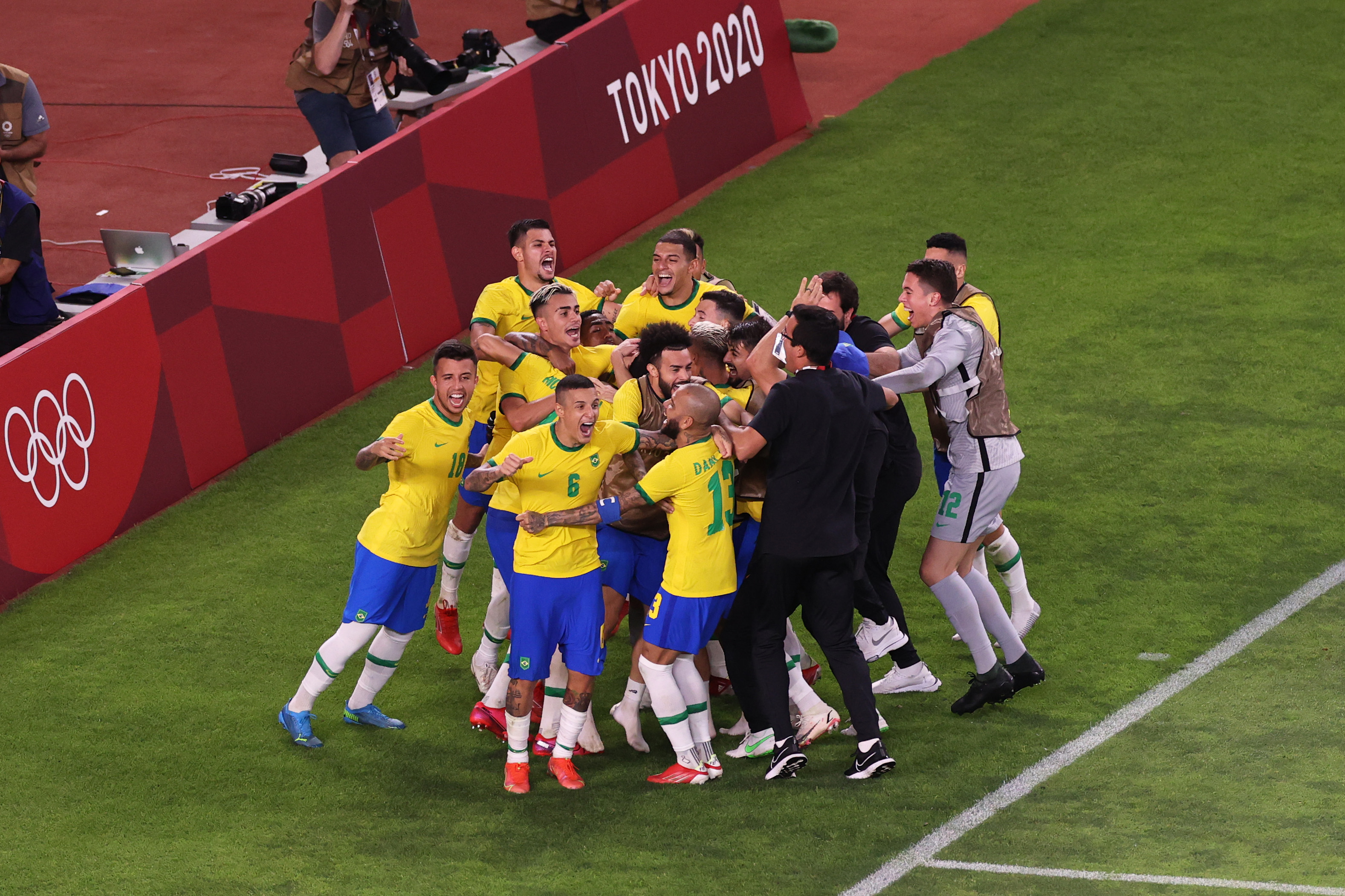 Reinier #19 of Team Brazil (obscured) celebrates with team mates after scoring their side's winning penalty during the penalty shoot out during the Men's Football Semi-final match between Mexico and Brazil on day eleven of the Tokyo 2020 Olympic Games at Kashima Stadium on August 03, 2021 in Kashima, Ibaraki, Japan.
