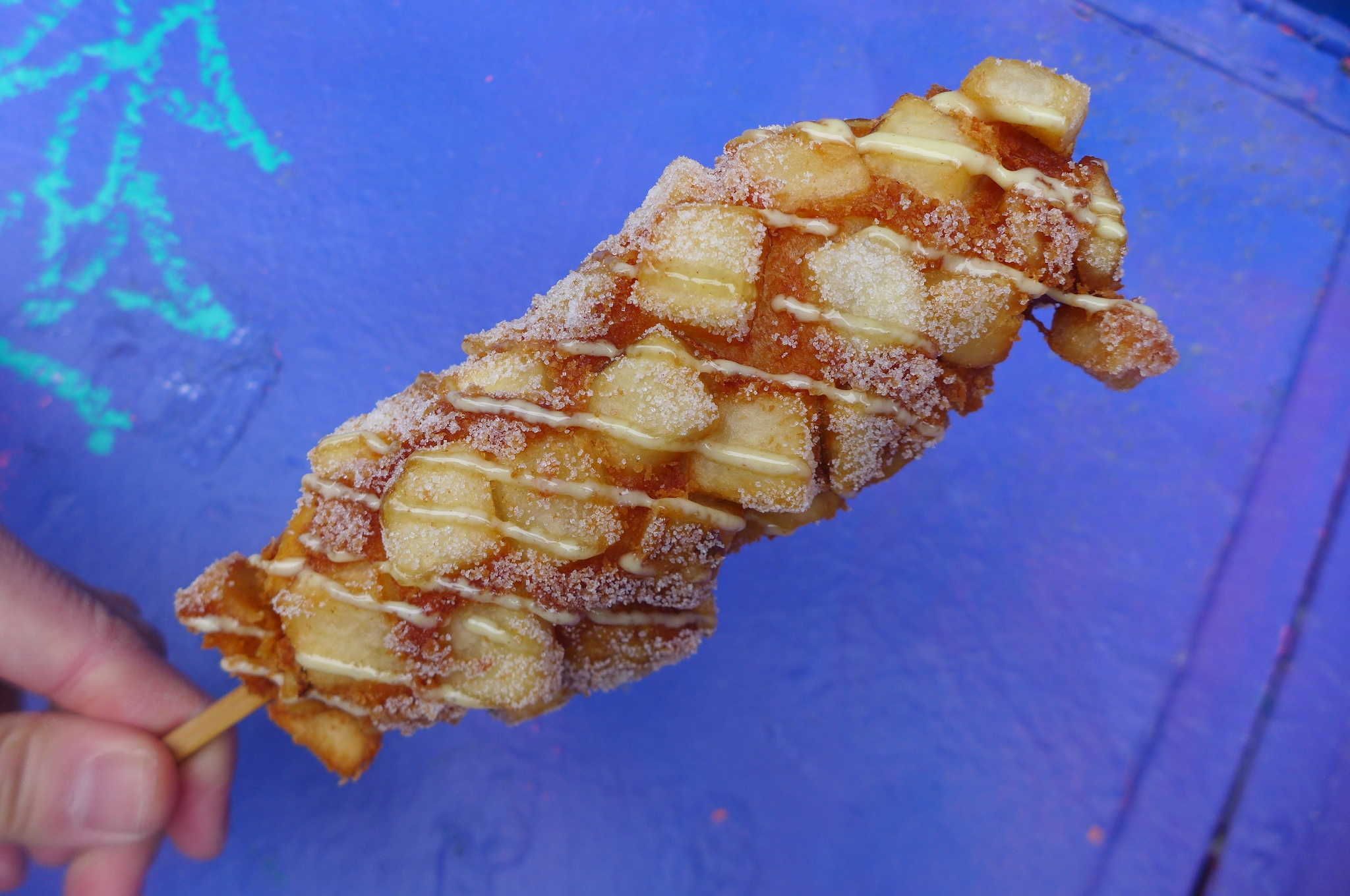 A corn dog with potato cubes in the batter held up against a blue background