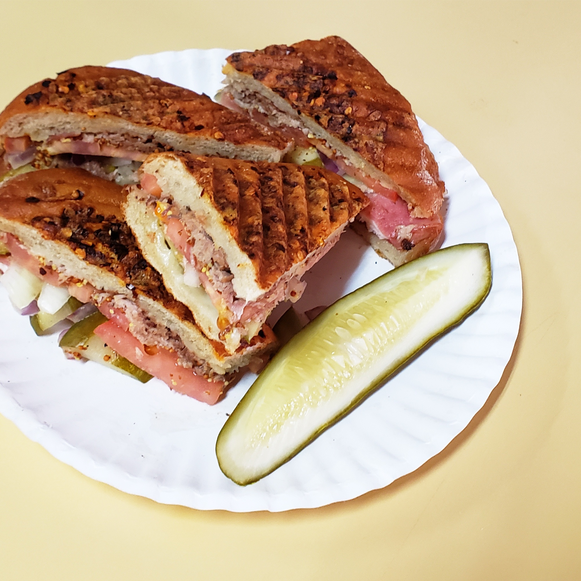 a grilled sandwich on a paper plate with a pickle spear