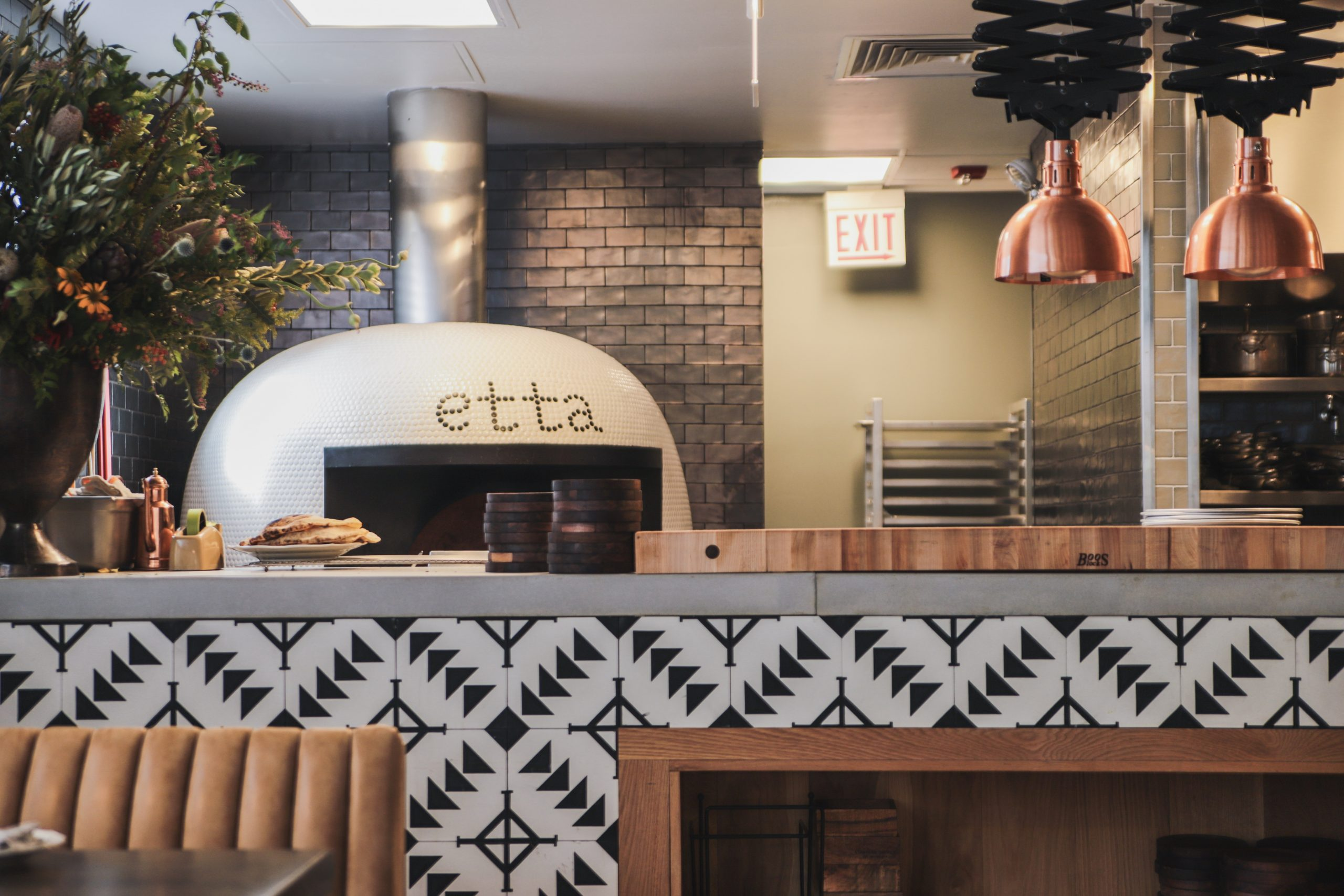 A side view of a wood-fired oven and bar seating at a new Italian restaurant that's about to open.