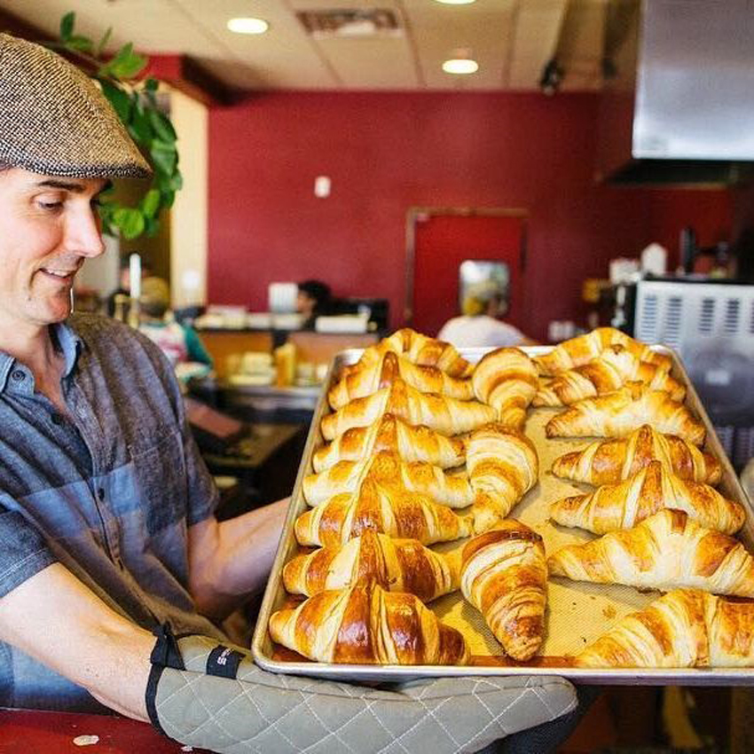 Owner Olivier Brouillet holds a tray of in-house made croissants at the Baguette Café.