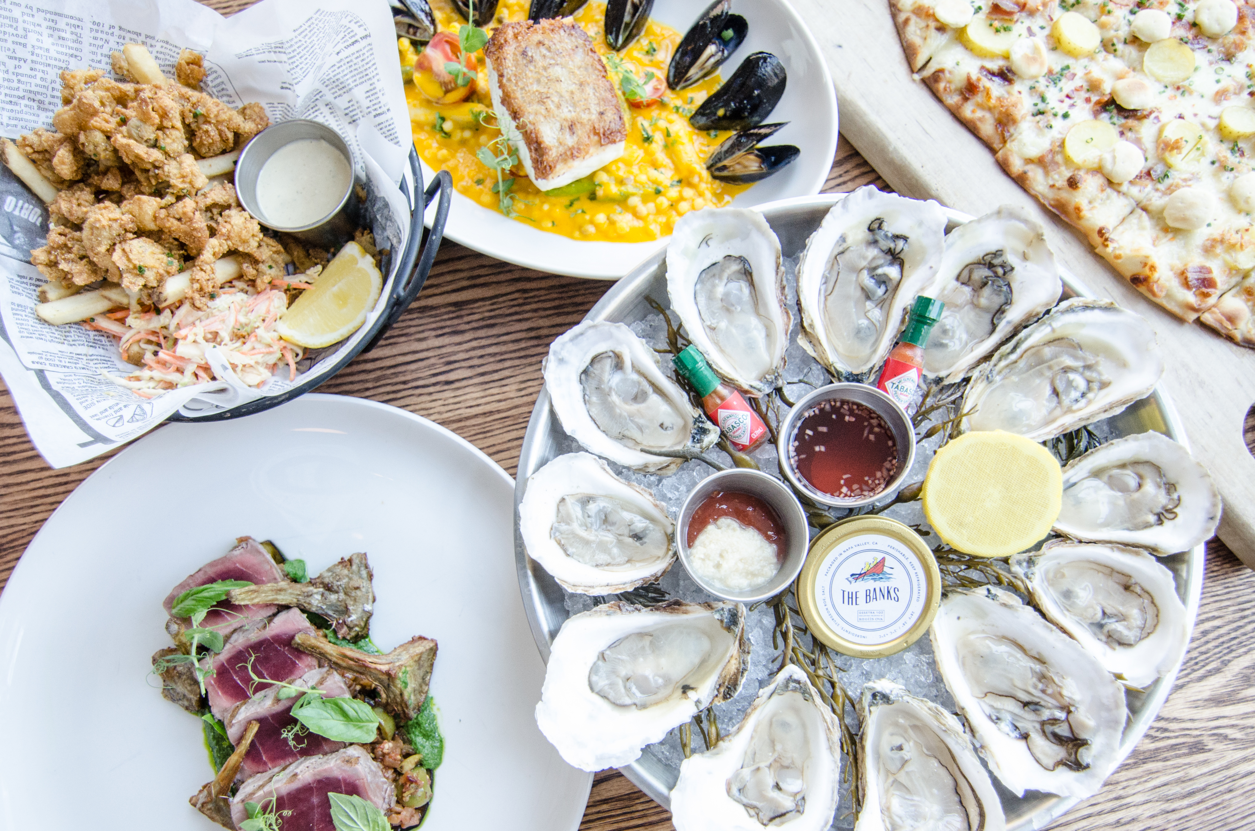 Overhead view of a table full of seafood dishes, including a platter of oysters, a basket of fried clams and fries, rare bluefin tuna, and more