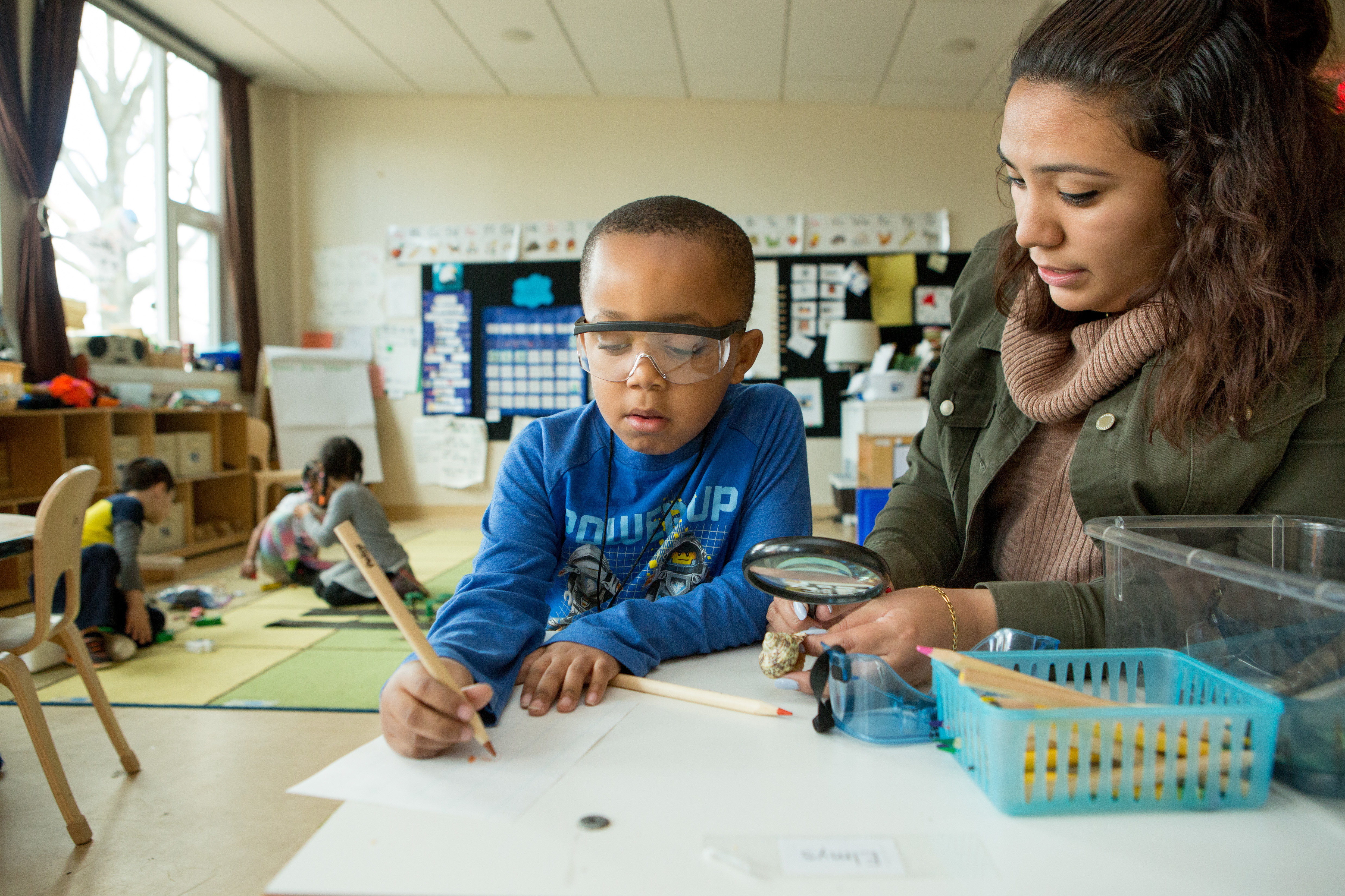 A teacher sits at a table with a kindergarten boy who is looking at a paper using a magnifying glass.