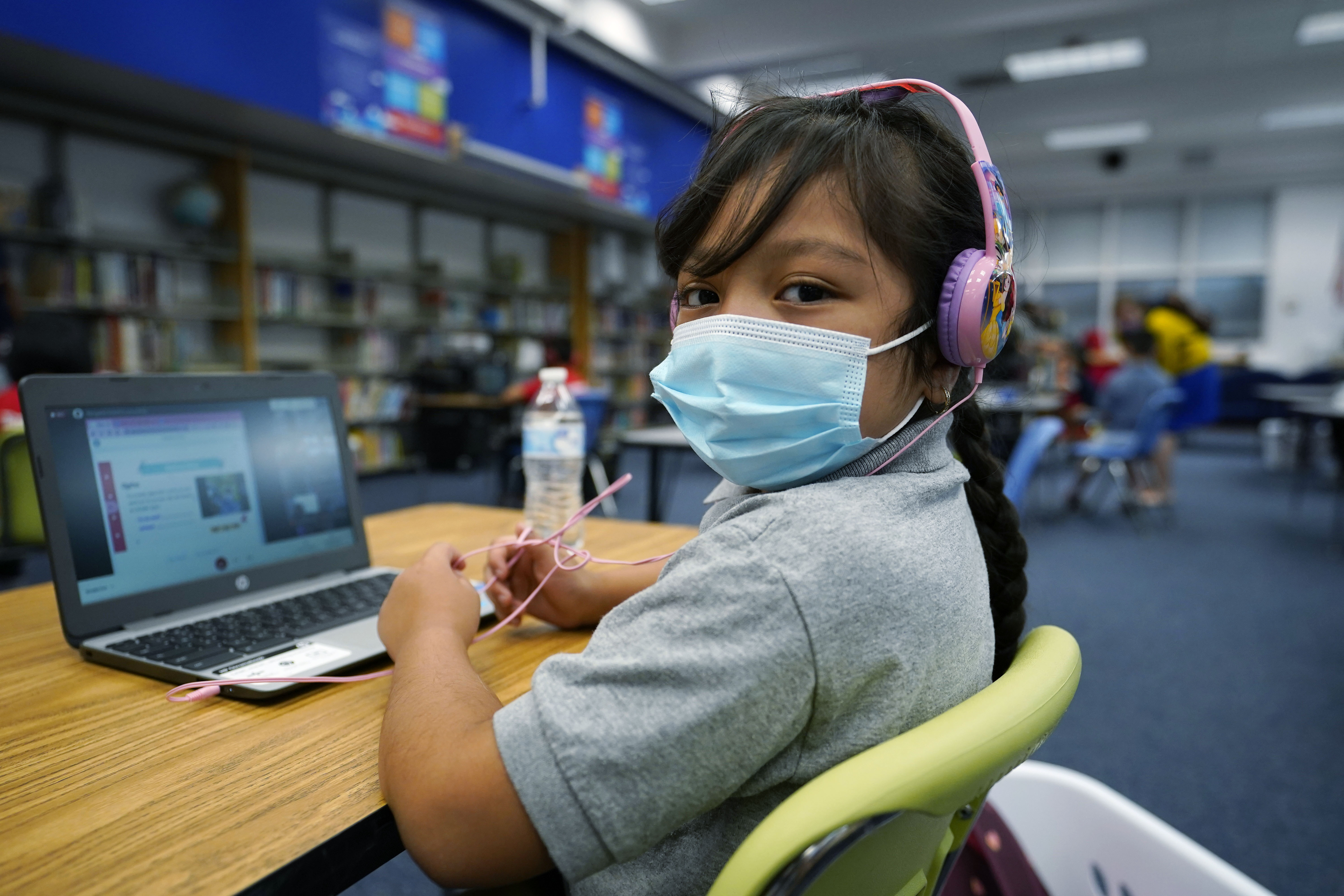 Masked girl works on her laptop at a learning center.